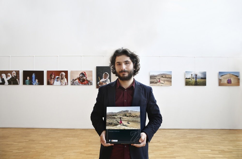 Nevzat Yıldırım standing in front of exhibition of his photography, holding one of his images