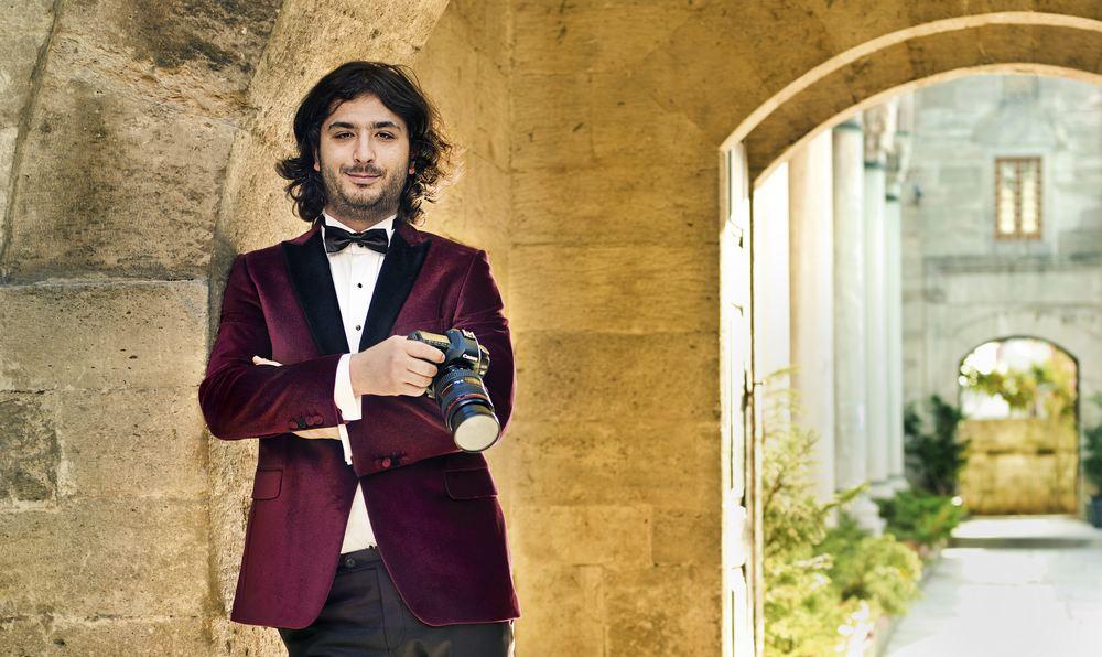 Nevzat Yildirim in tuxedo holding camera