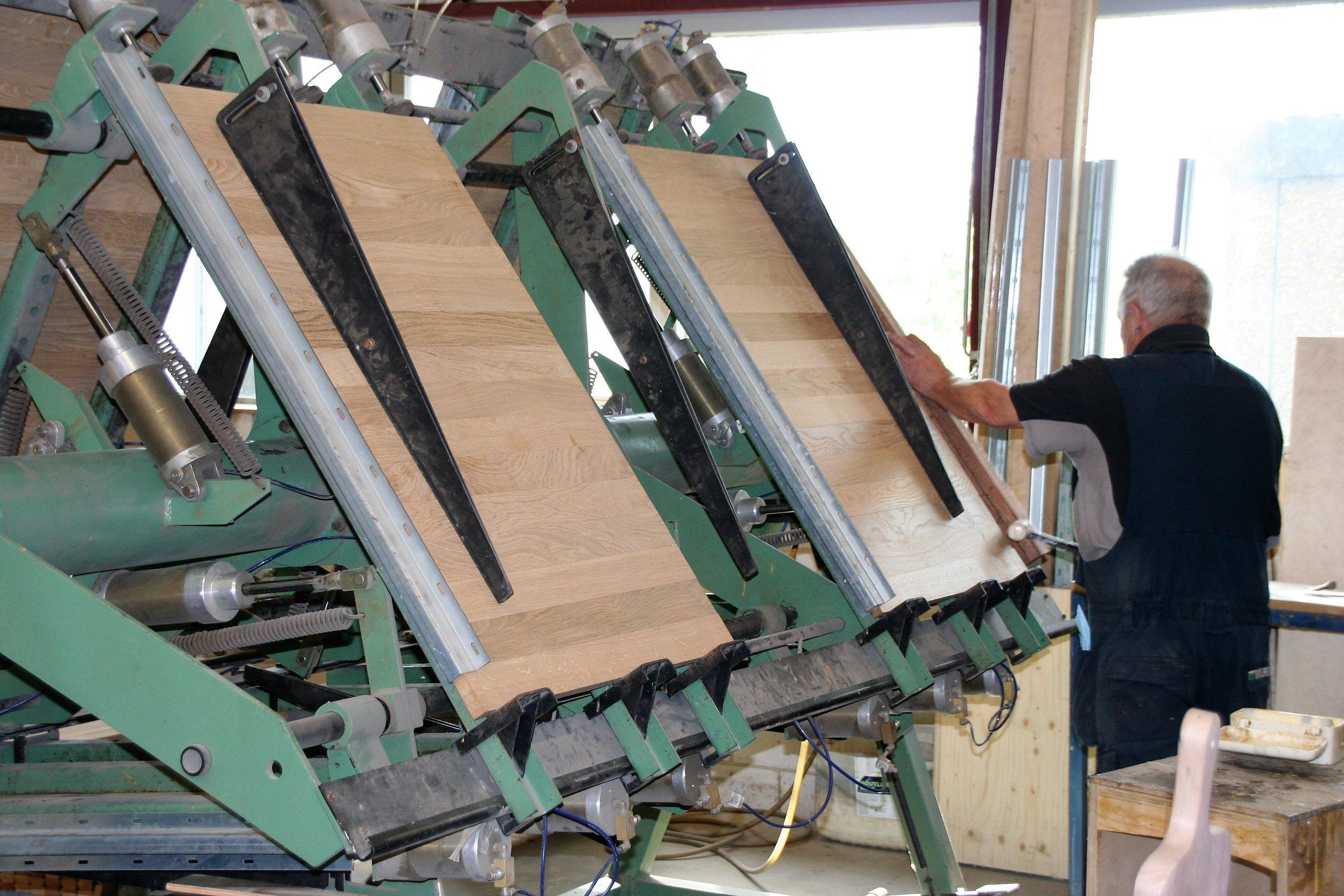Verlijmen - Massief houten stroken worden verlijmd tot panelen waaruit op de CNC-freesmachine de gevraagde producten worden gefreesd.