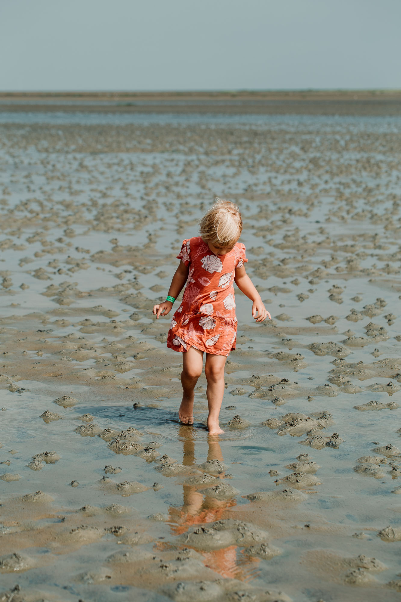 Edith on the beach.  (ID: A child in an orange dress stands on a sandy beach with only a little water on)