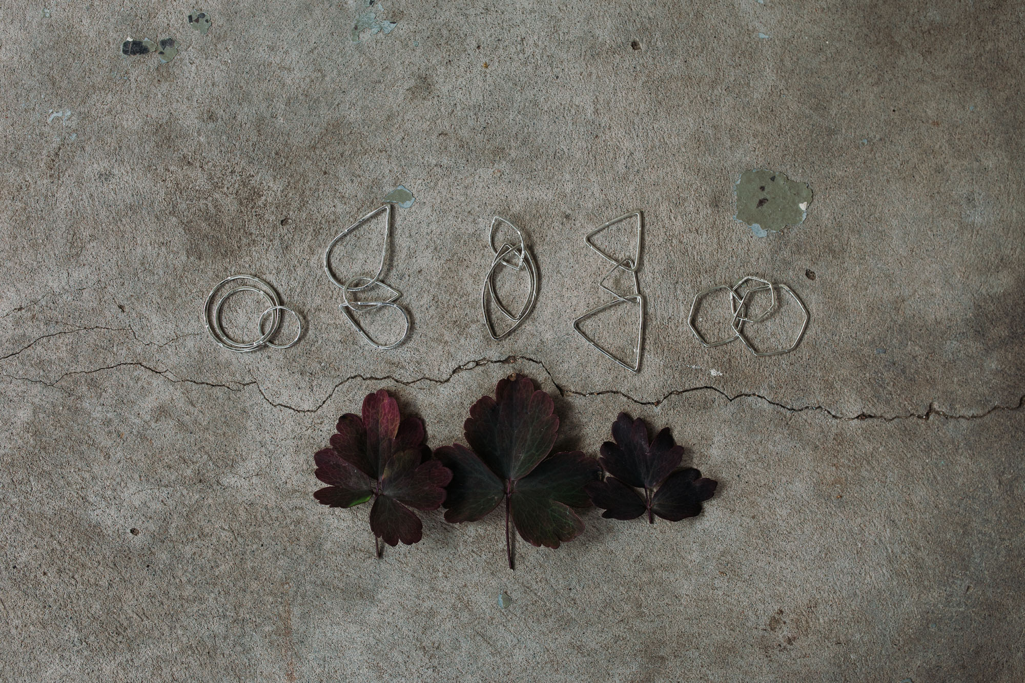 The primary line; Sphere, Drop, Leaf, Mountain and Crystal.  (ID: Five silver pendants lie on a cracked concrete floor, just above three dark red aquilegia leaves)