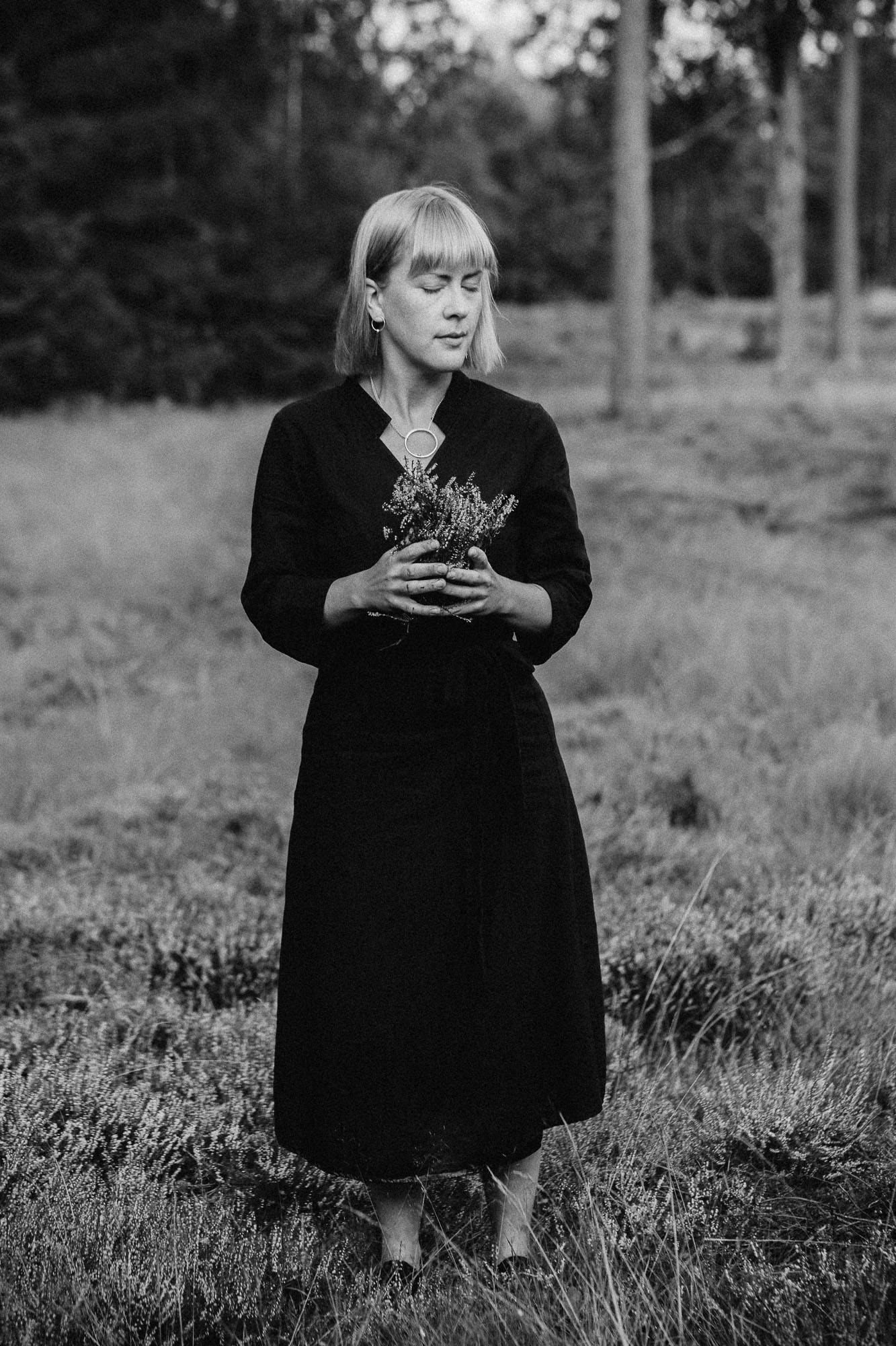 Me, August 2019, in the heather field.  (ID: A black and white photo of a woman in a black dress standing with her eyes closed and heather flowers in her hands in a field)