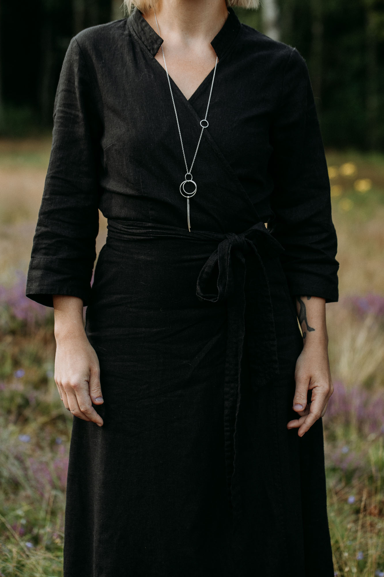 Sylvestris on Stitch 80 cm.  Photo ID: A woman in a black dress in a heather field is wearing a long silver chain from which a pendant with circles and needles hang.