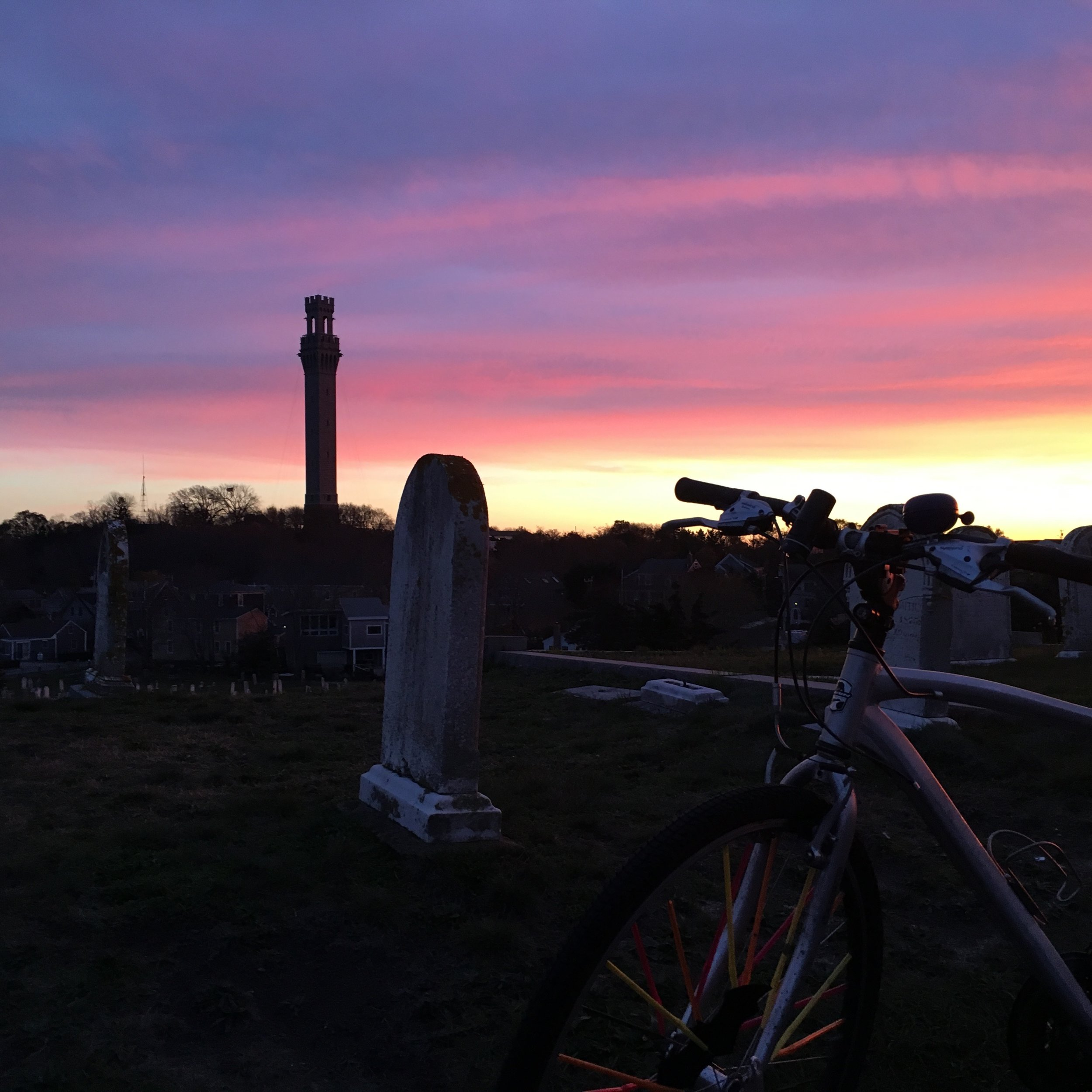 A stunning sunset behind the Pilgrim Monument seen from the cemetery in Provincetown (with a bike, of course).
