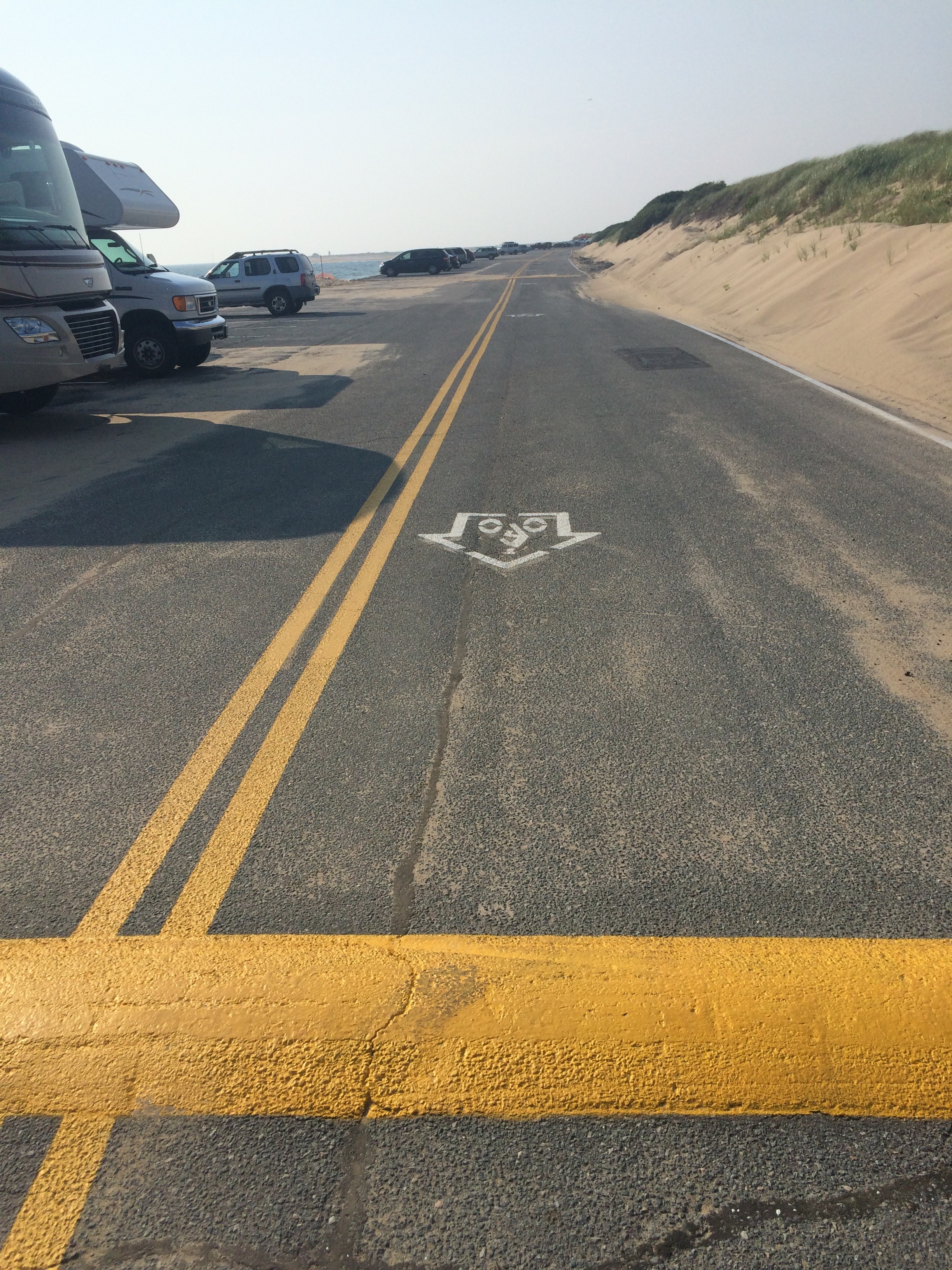 """An old-style """"bike in house"""" shared lane marking pointing in the wrong direction at the Herring Cove parking lot in Provincetown"""