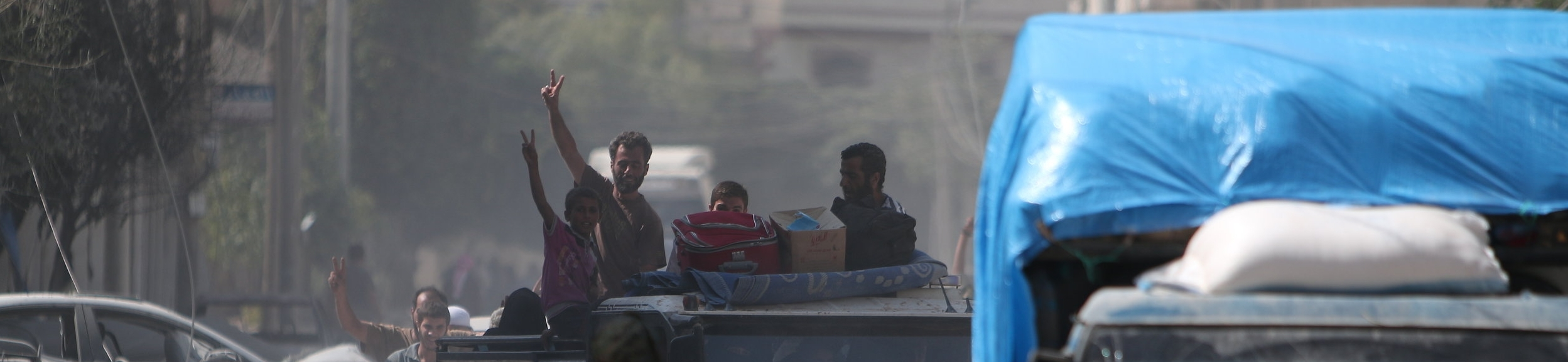 IDP's run from Daesh and wave to QSD fighter in Raqqa.JPG