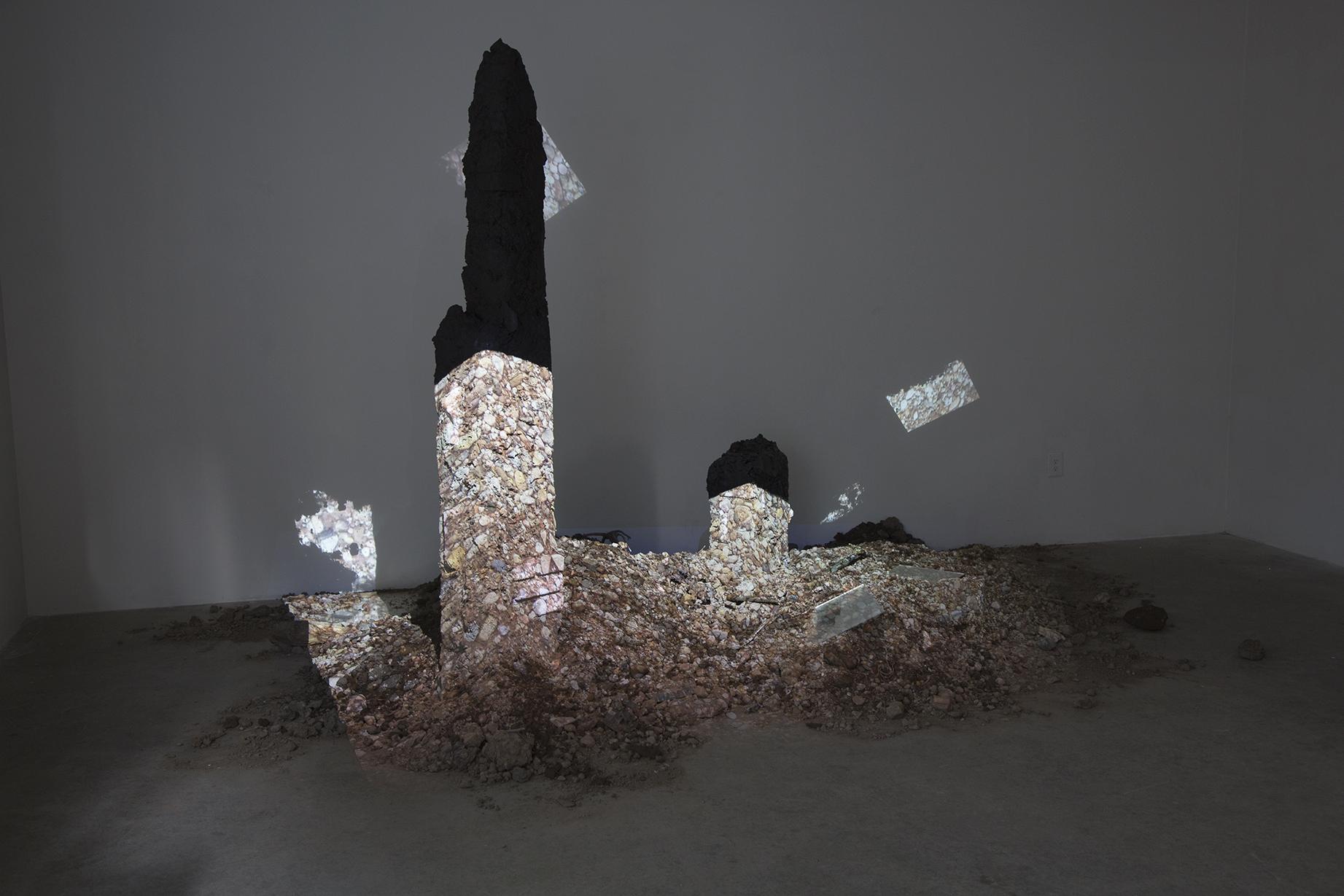 earth, stone, detritus, trash, brick, ammonite fossils, mirror, rubber, sticks, lichen, projected image of New Mexico ground; dimensions variable