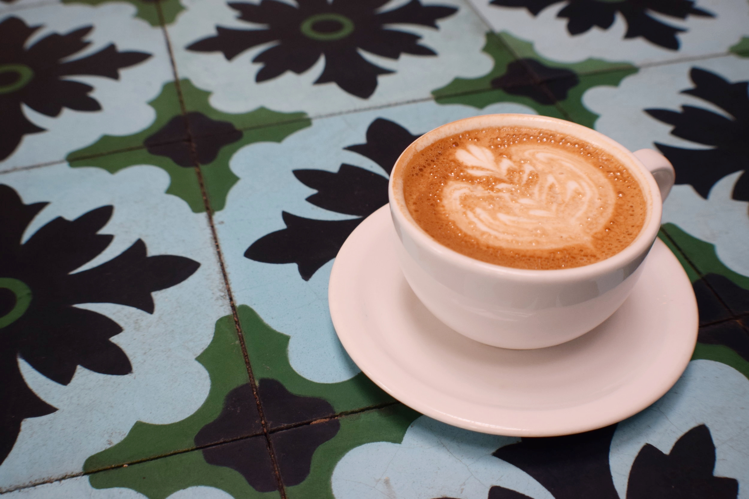 The foam art on Tipico's Honey Latte rivals the pattern on the colorful tile adorning the historic stone heater that doubles as bench.