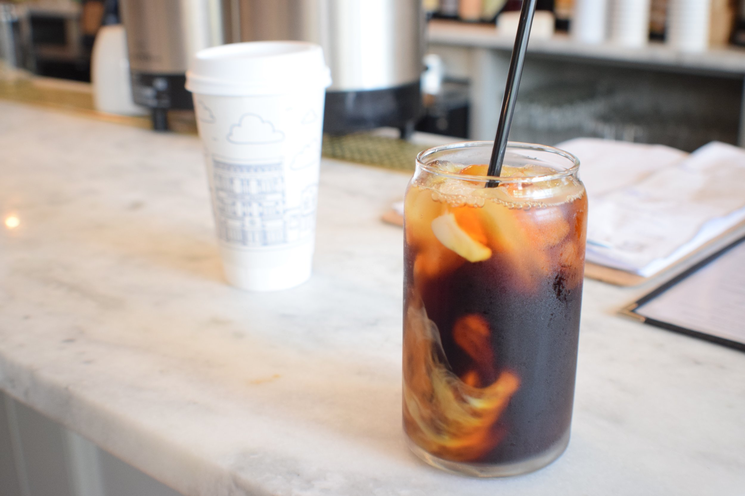 Milk swirls in our coffee-for-here; drinks are also available to go (in the cutest cups ever)