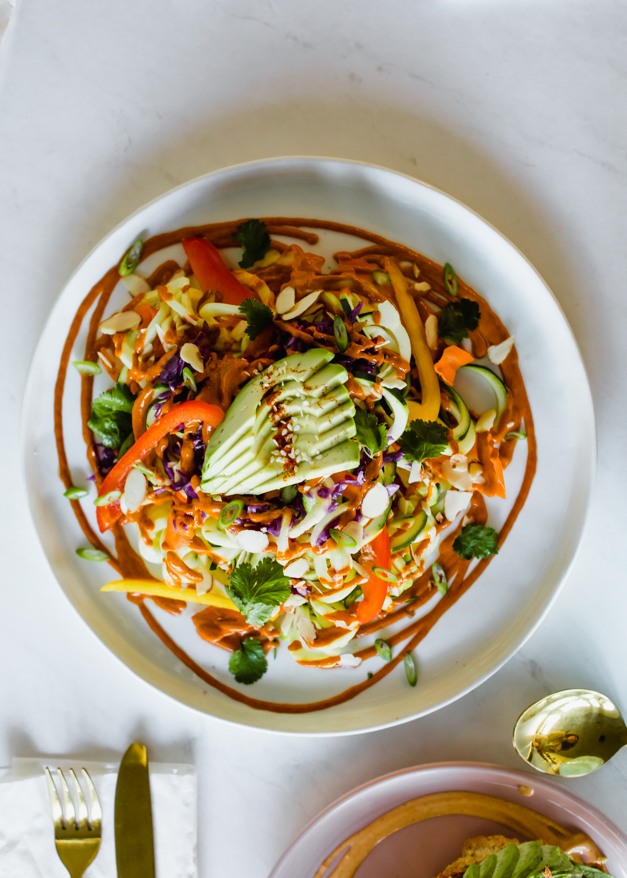 Fully Raw Pad Thai (Cold) - Made up of zucchini noodles, pickled carrots, raw sauerkraut, avocado, bell pepper, cilantro and topped with an incredible sauce. A plant based twist on a Thai classic, Wholism fully delivers on this raw dish.