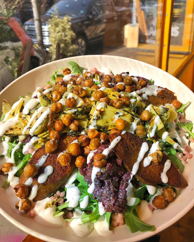 Forever dreaming about our Dream On! bowl 💭🥗😍 filled with house-made seitan based spicy merguez sausage, artichoke hearts, pink couscous, fresh peppery arugula, a dollop of olive tapenade, and house-made lemon garlic aioli 🍋