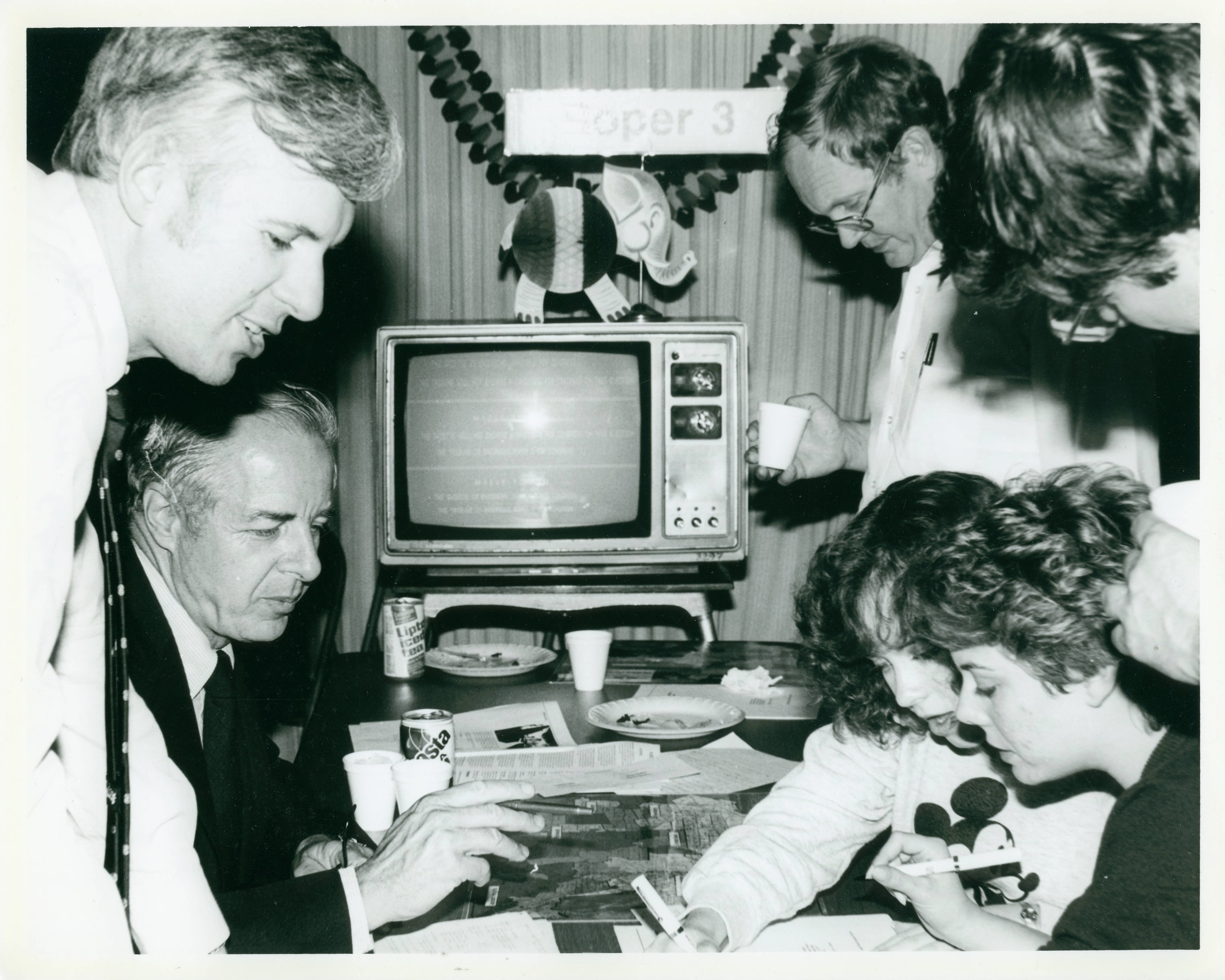 Professor Ross Eckert (left) and other faculty and students go over documents. Image credit: Claremont Colleges Photo Archive