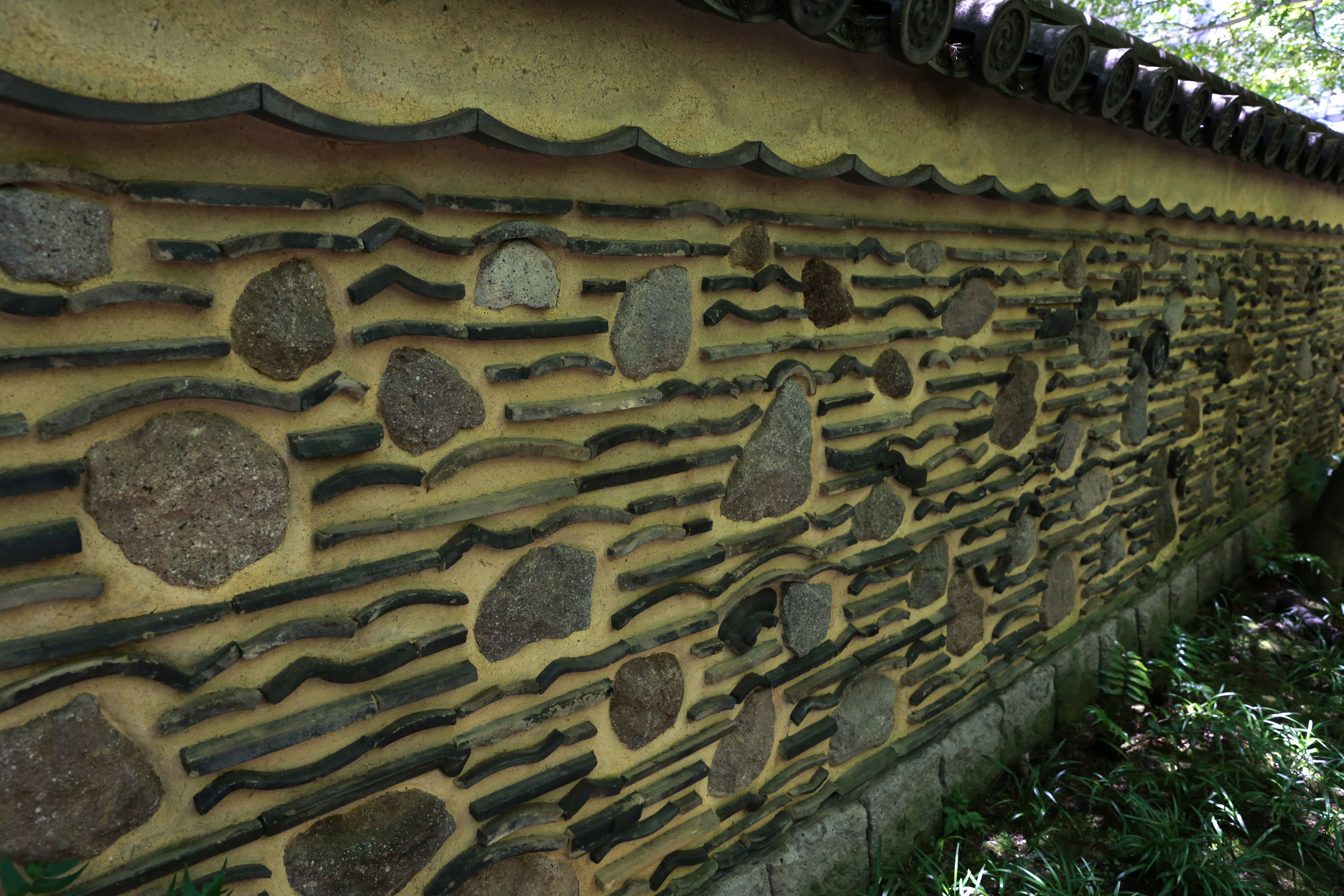 Hakatabei walls surround the Rakusui-en's garden and tea rooms in Fukuoka, Japan, June 22, 2018. The Rakusui-en's hakatabei wall dates back to the Sengoku period and is made up of recycled tiles, rocks, and dirt.