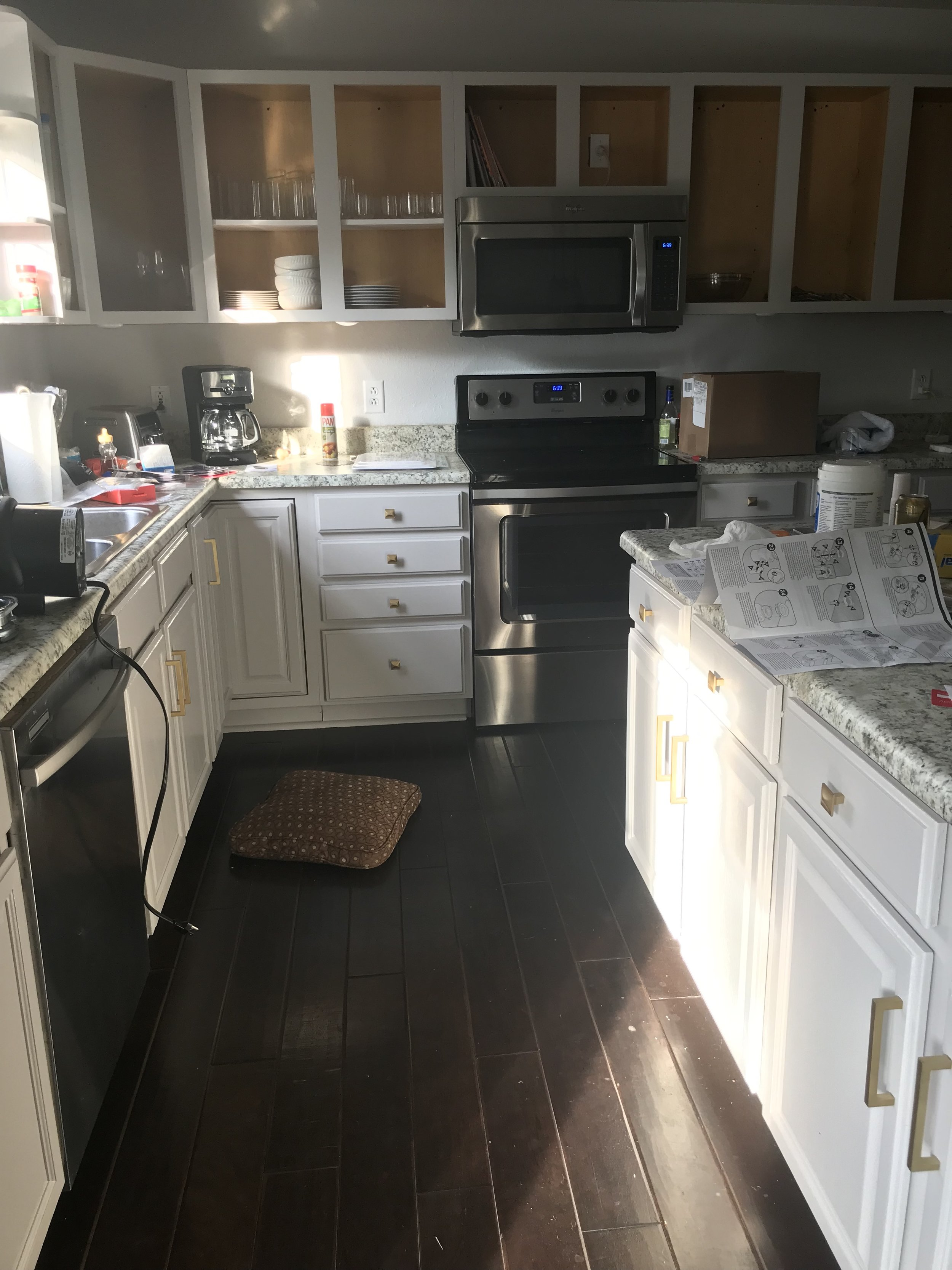 DURING: Kitchen cabinets halfway finished. Disregard the mess - we are attempting to replace the broken garbage disposal and we have no idea what we're doing.