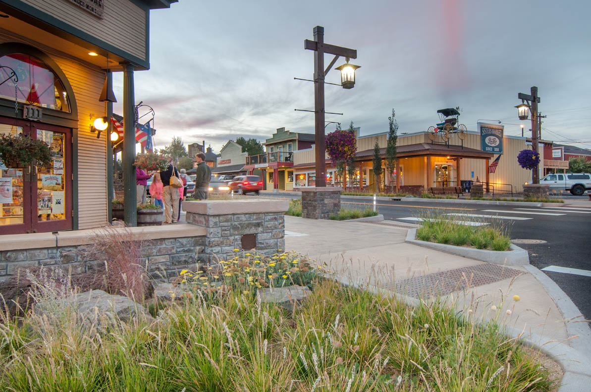 people gather on a sidewalk behind landscaping and a stone wall, lit lampposts form a gateway for a crosswalk