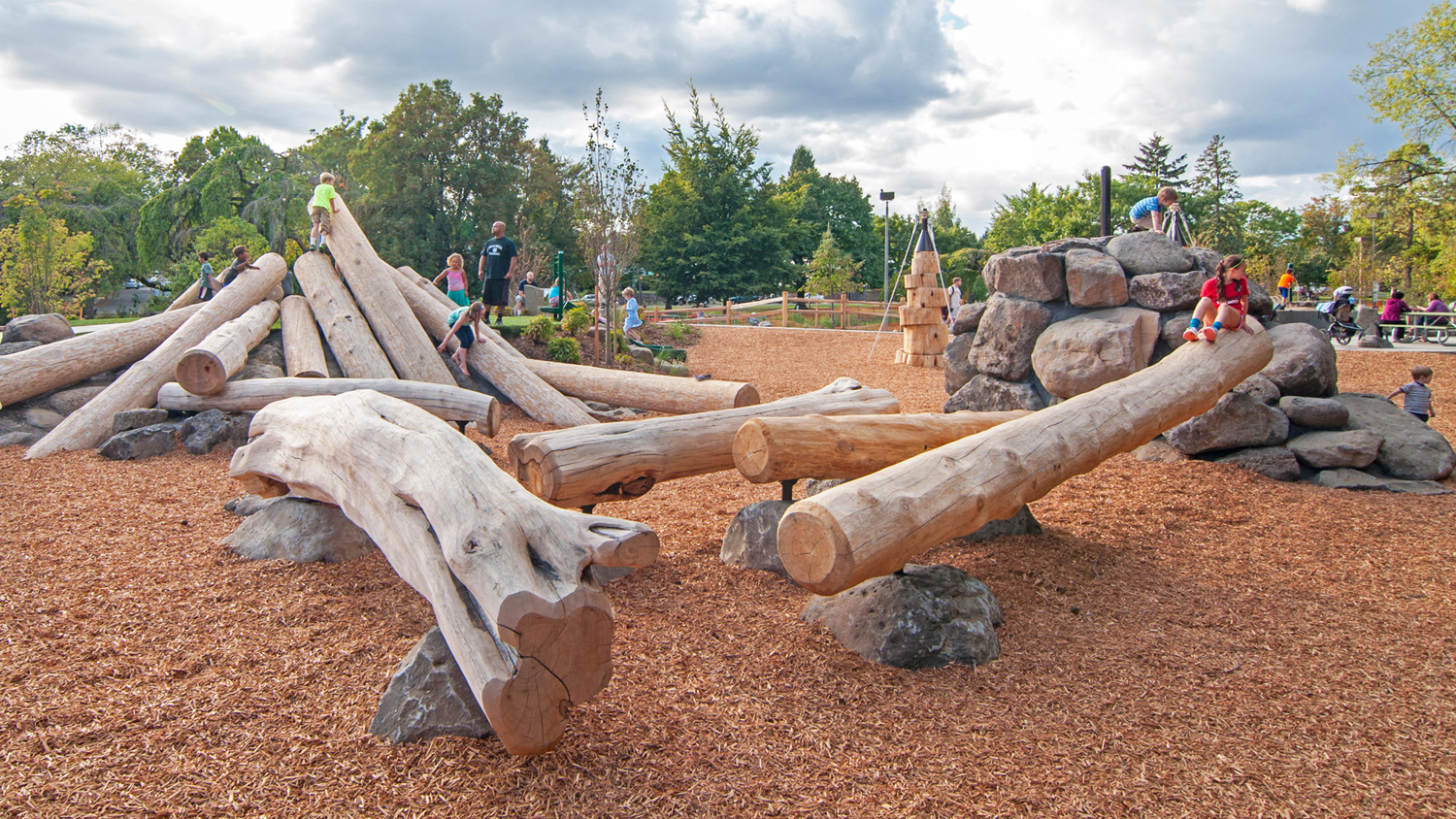 logs come to a point with children climbing, standing on piles of rocks on a cloudy day