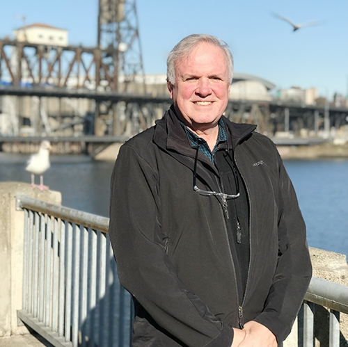 Mike Faha standing in front of willamette river and steel bridge