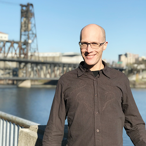 Andrew Holder standing in front of willamette river and steel bridge