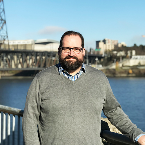 Jason King standing in front of willamette river and steel bridge