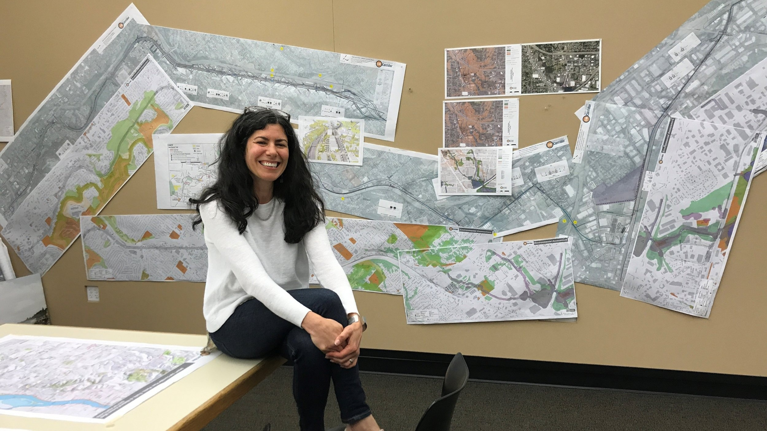 Jennifer D'Avanzo in front of SW Corridor plans that take up an entire wall at GreenWorks HQ