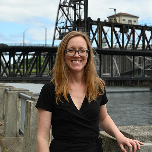Fay Savage standing in front of willamette river and steel bridge
