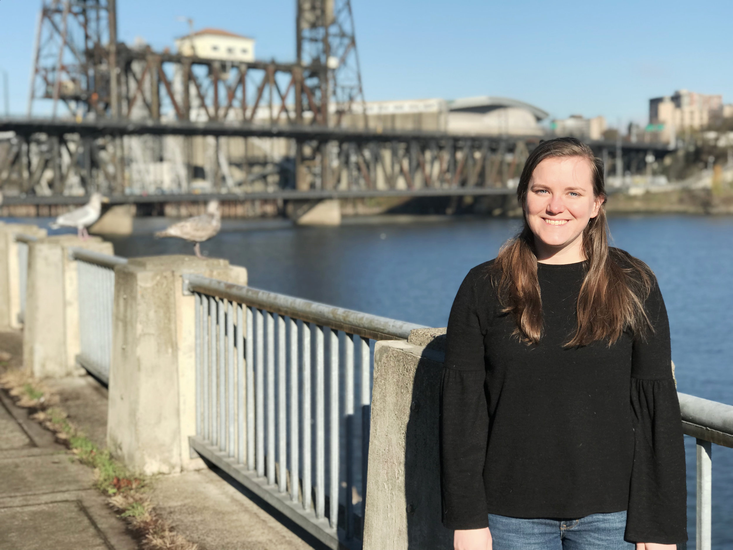 Katie Schneider stands in front of the willamette river and the steel Bridge in portland
