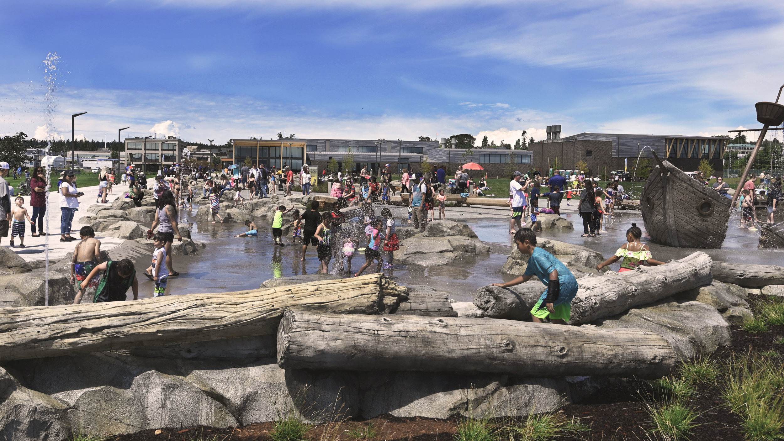 children play in shipwreck shores during its grand opening day, logs and a shipwreck spout water