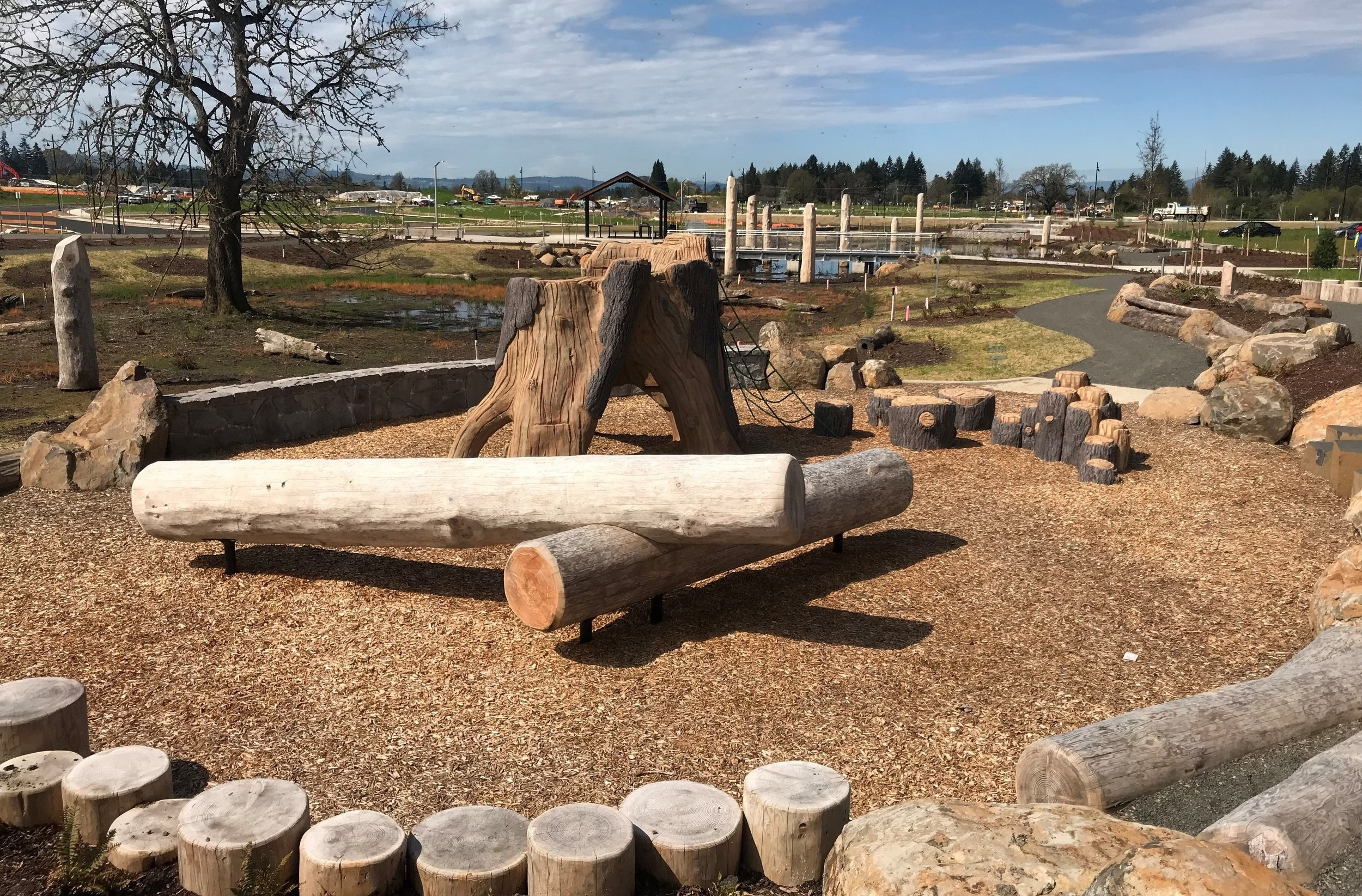 Logs and stumps in wood chips make a natural play area on a sunny day