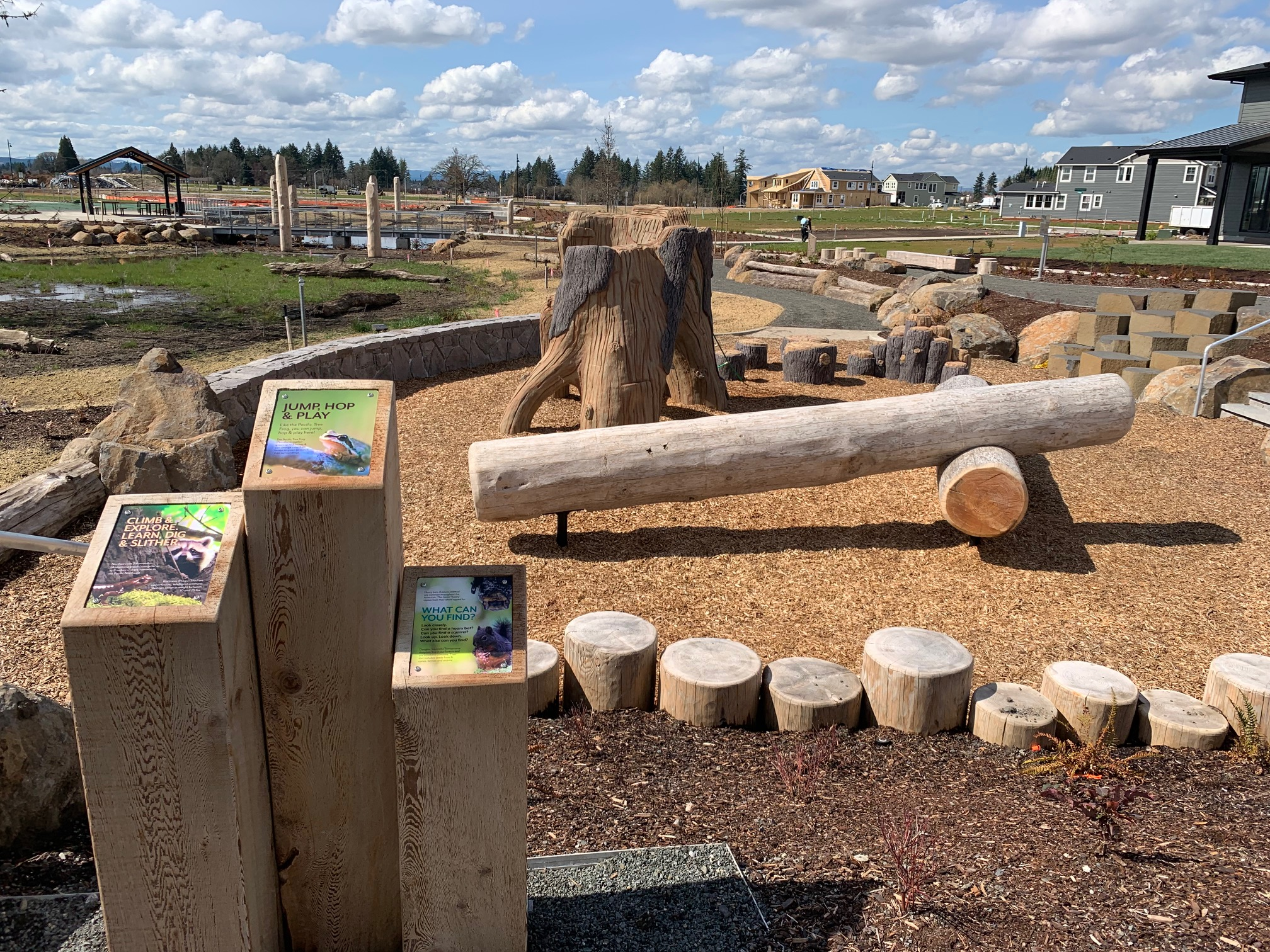 Interpretive signs in front of log climbers in wood chips on sunny day