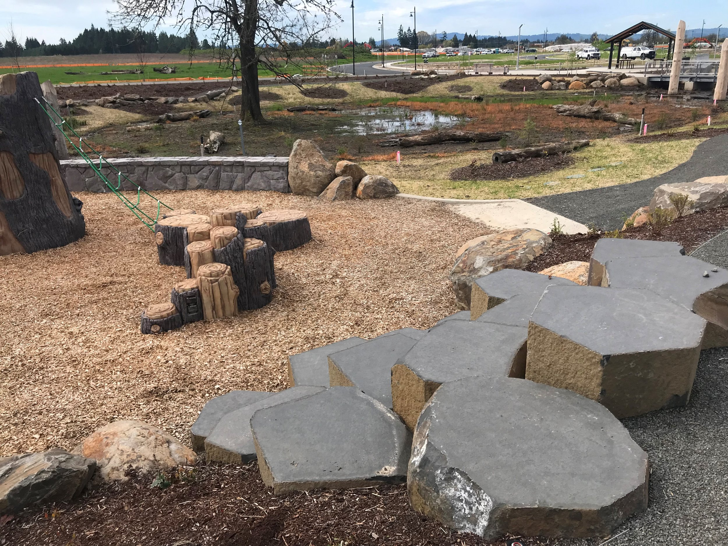 Basalt columns in front of wood chips and nature play area