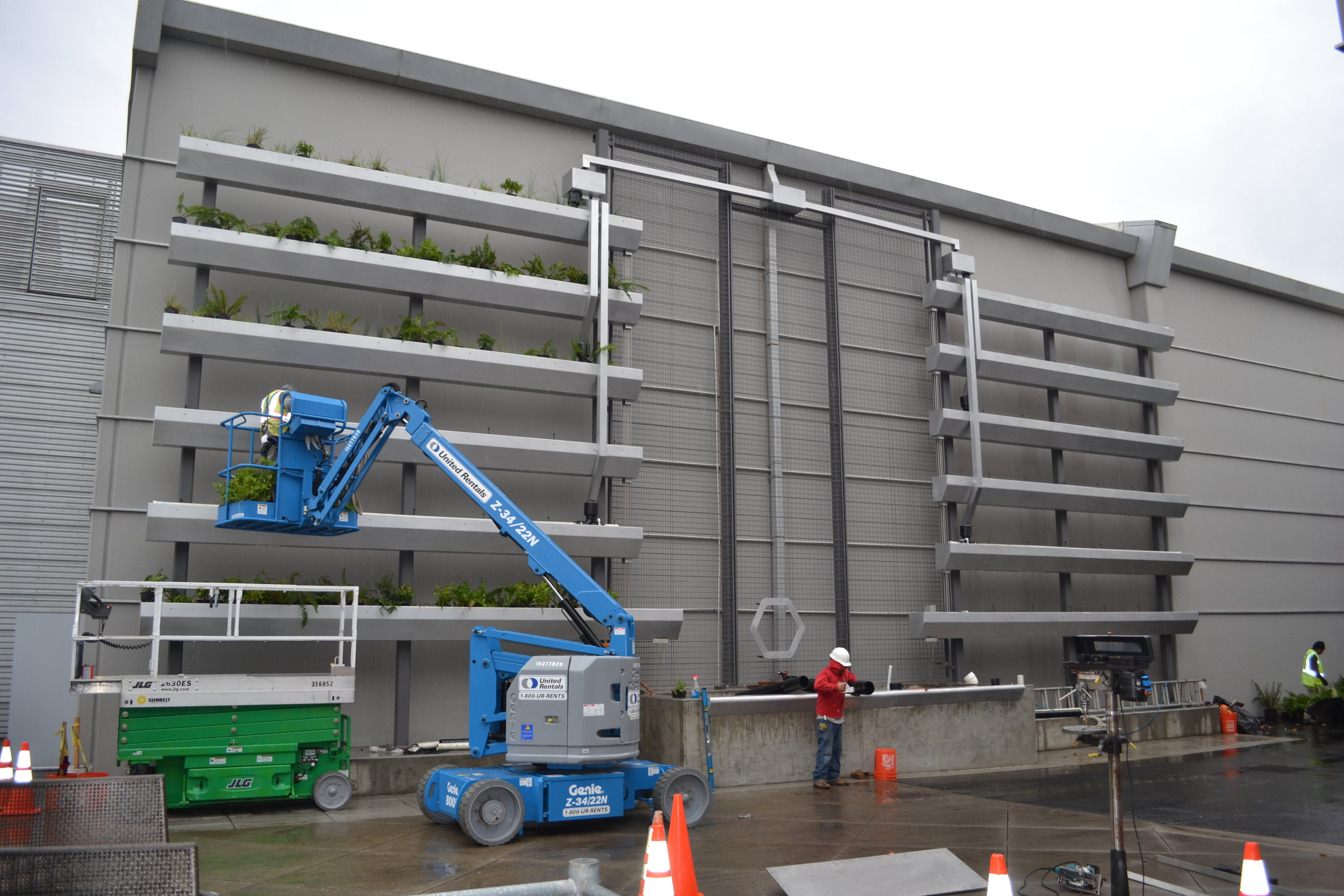 Stormwater wall under construction using cherry picker with men in hardhats