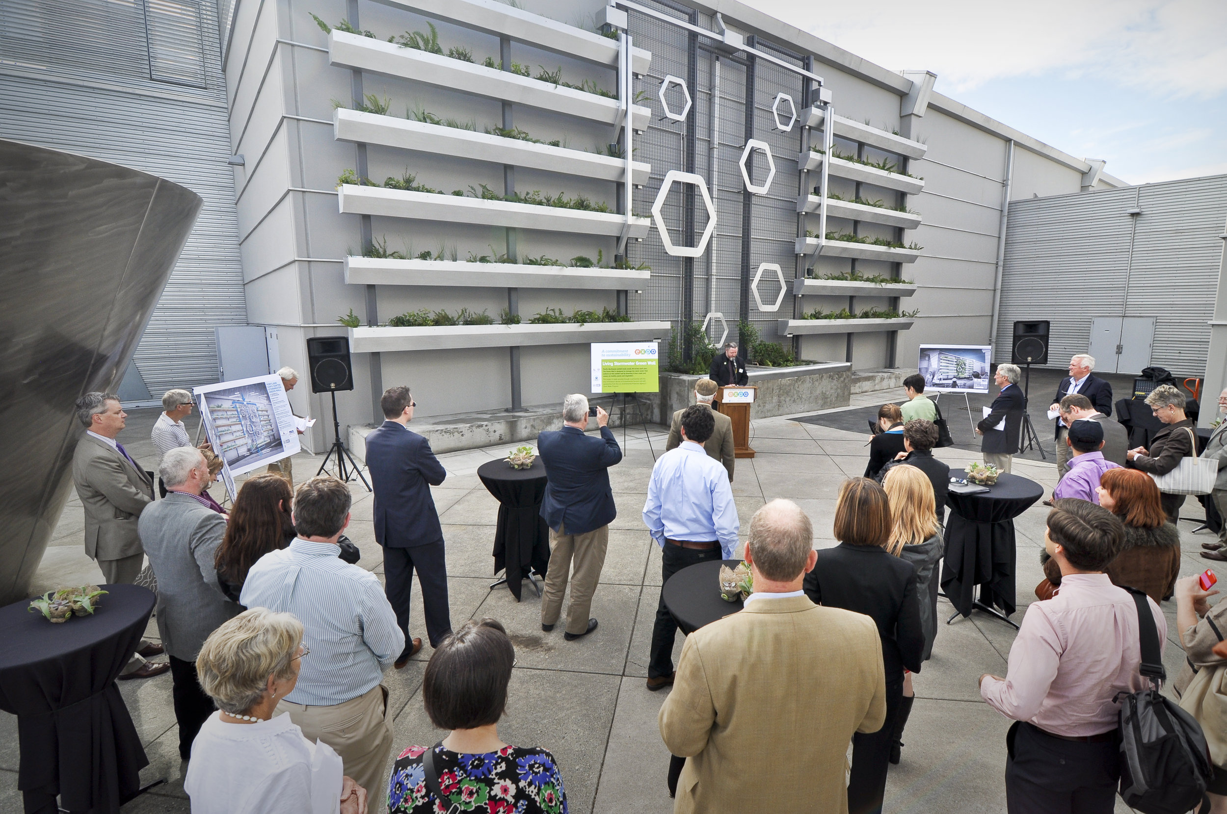 crowd gathers at grand opening of metro stormwater wall, empty podium at the center