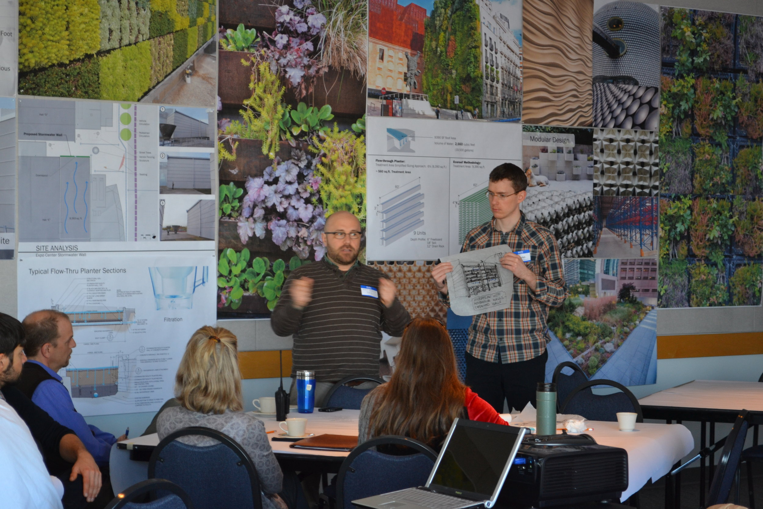 two greenworks staff explain stormwater wall to gathered group in office
