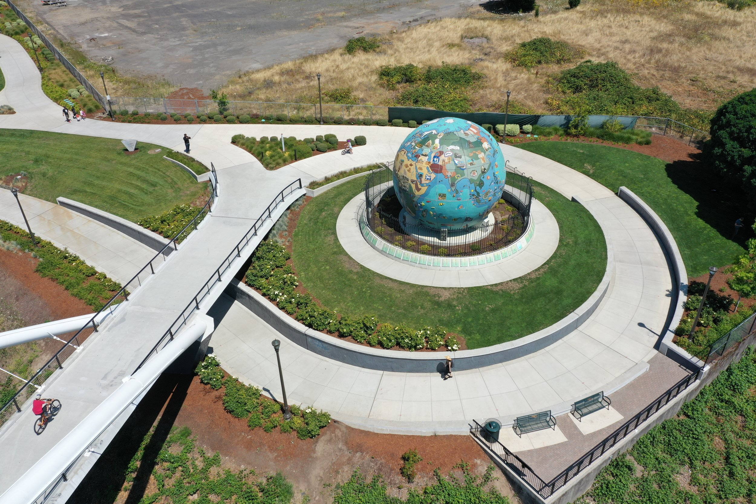 globe in site design with grass and sidewalks and a bridge footing