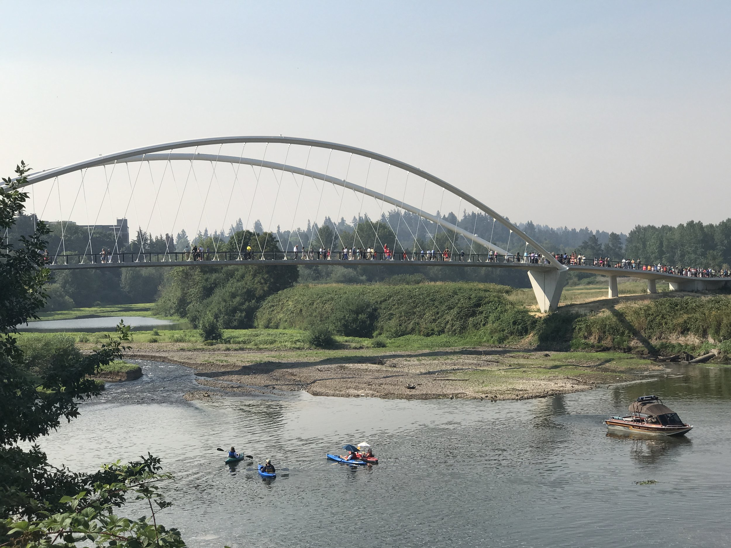 large crowds gathered at a grand opening, kayaks in river, people on suspension bridge