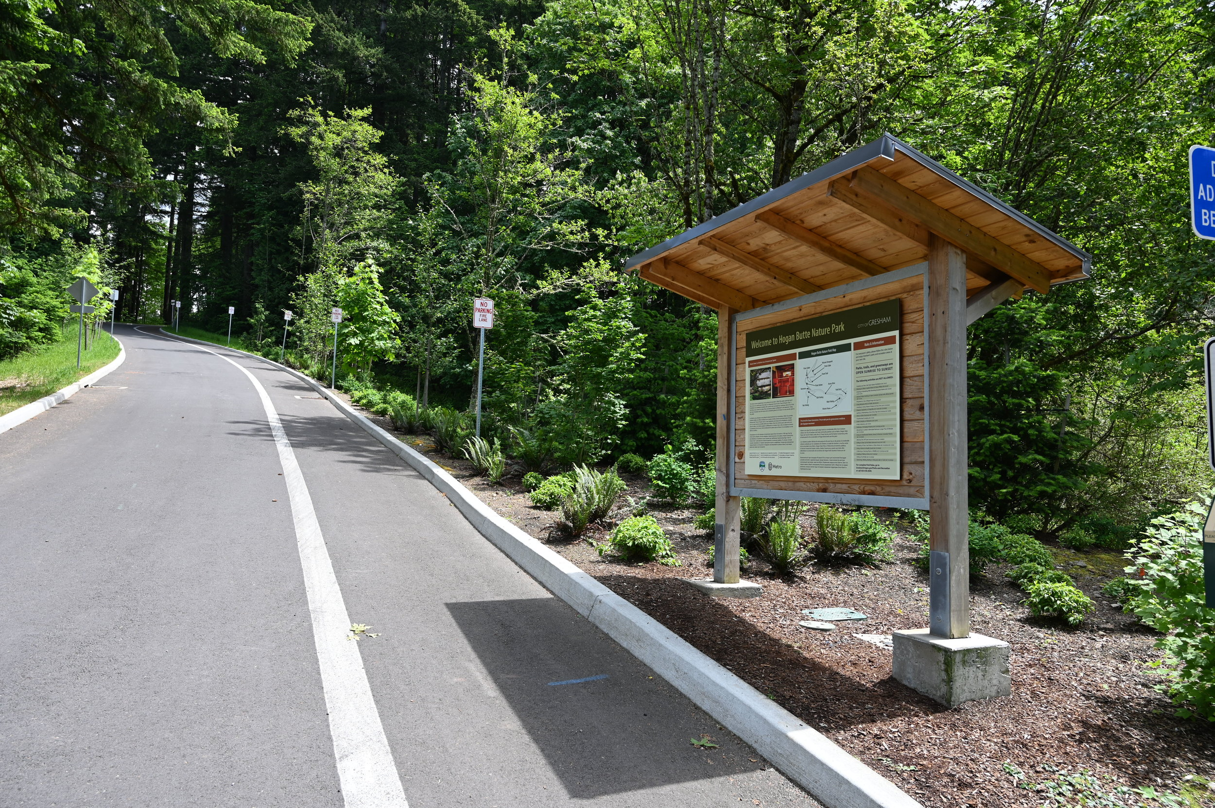 road winds up hill past interpretive sign