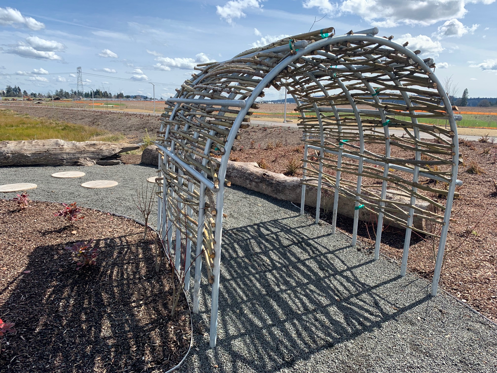 metal structure creating a tunnel with willow boughs weaved in nature playground