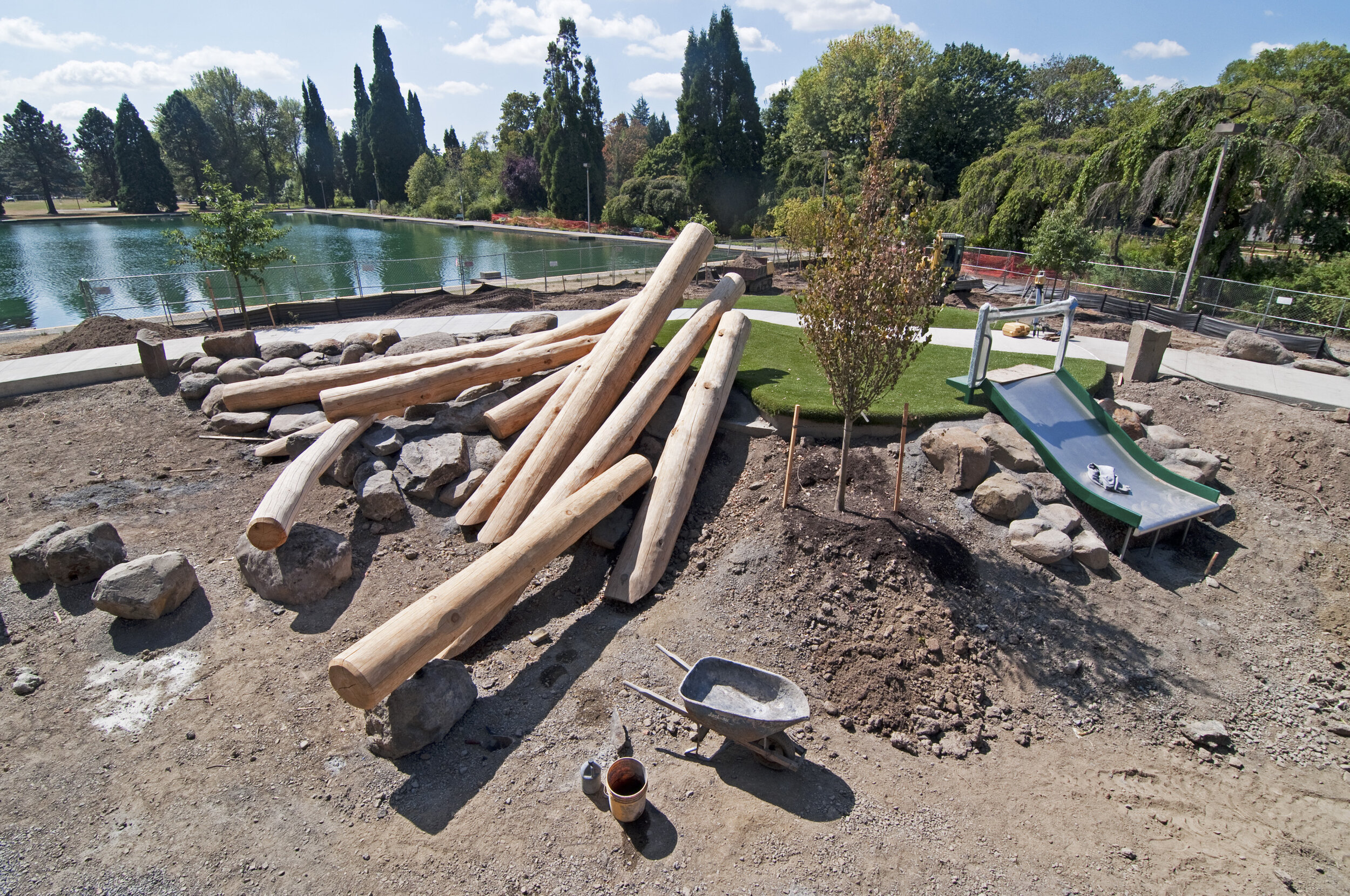 stacked logs, grass, a pond during westmoreland park construction