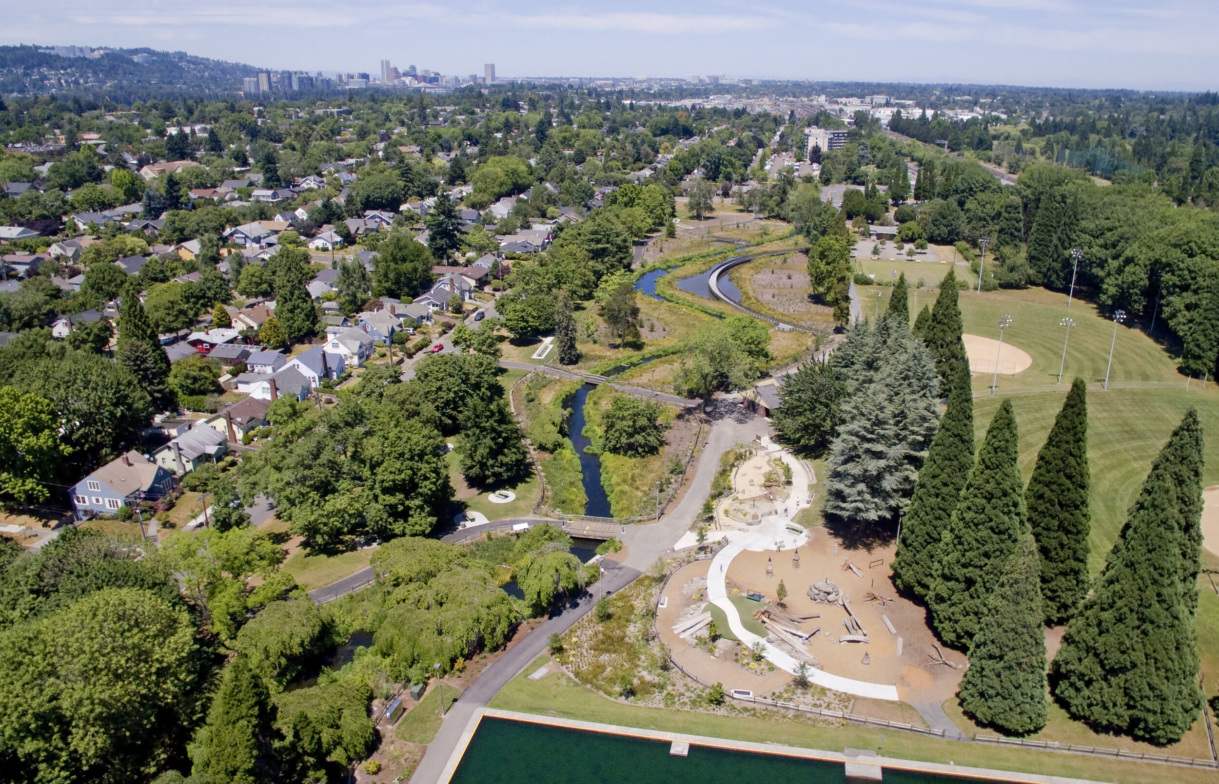 aerial of pond in front of nature play area, portland skyline in distance