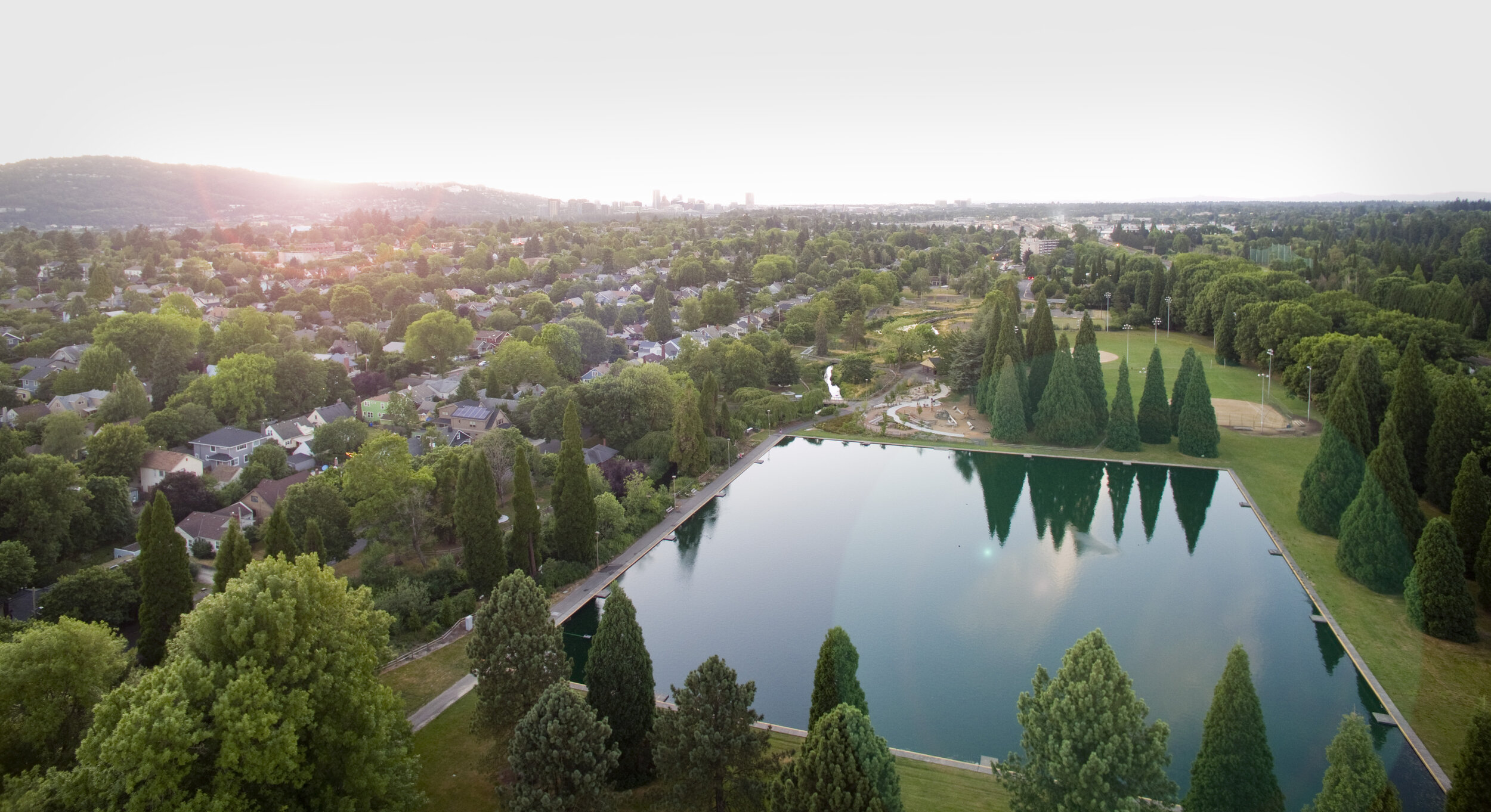 aerial shot of westmoreland park, pond in foreground, nature play area visible, portland skyline in distance