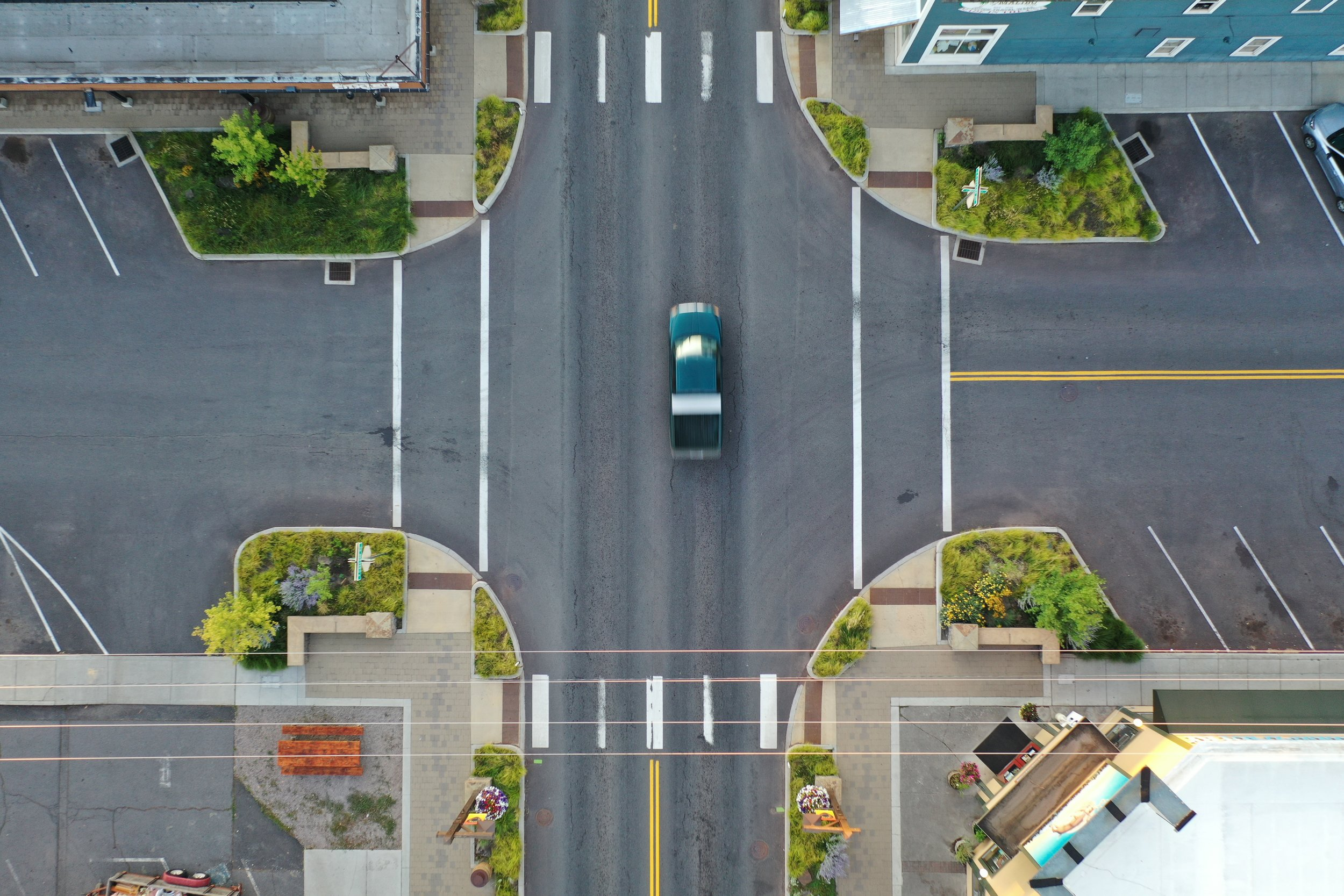 aerial photo of moving car in intersection surrounded by green planters in sisters, oregon
