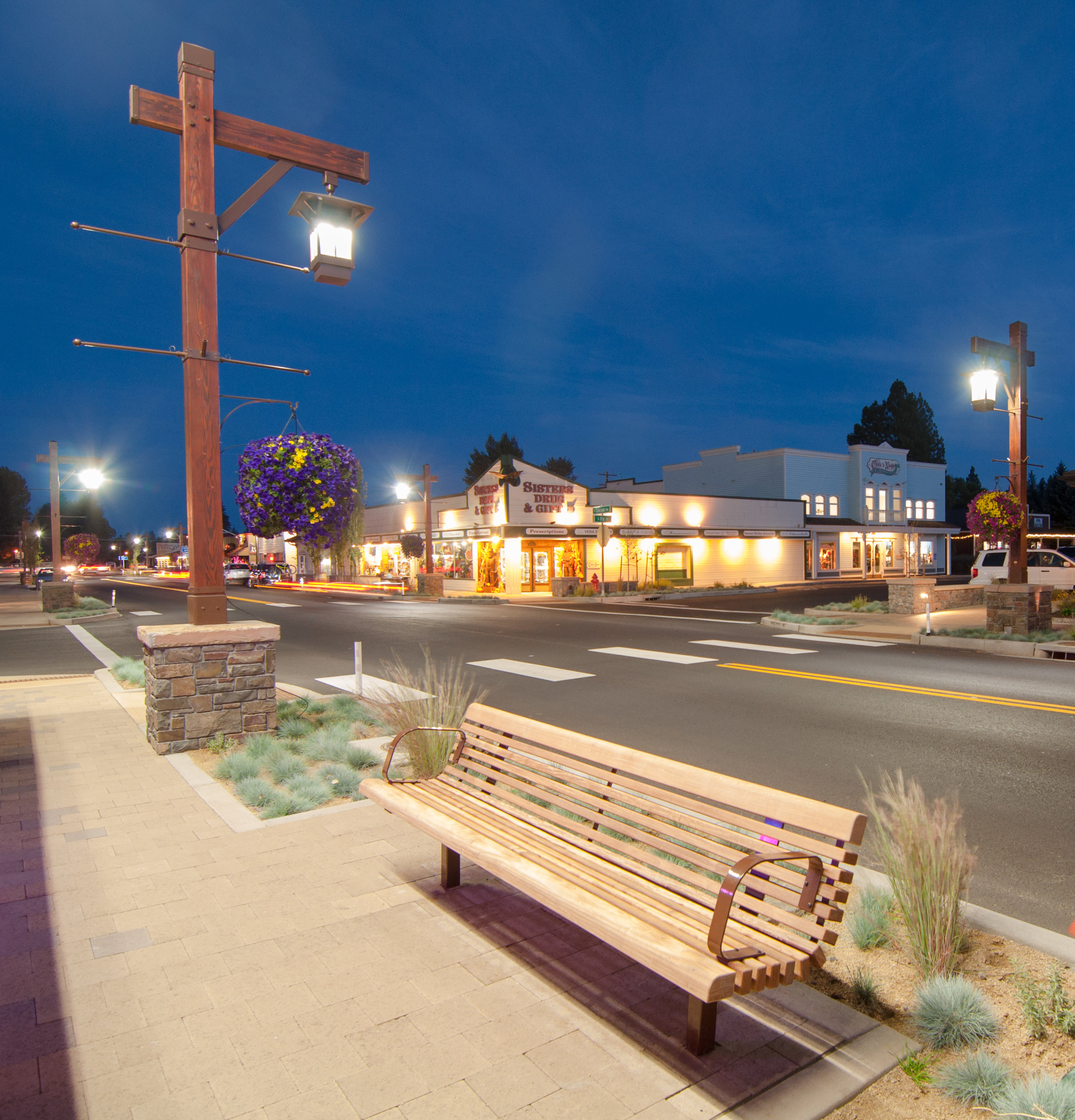 twilight street with lit lamp posts, a bench, and grasses lining highway 20