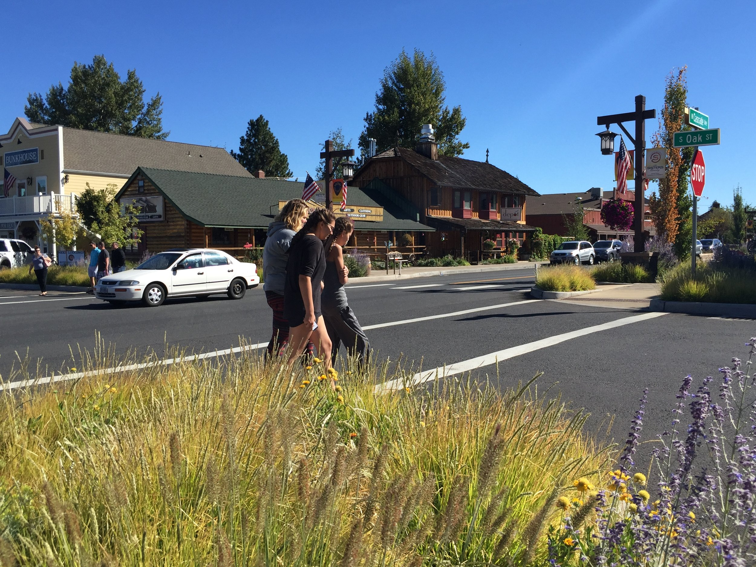 people cross highway 20 in sisters, grasses in streetside planters in foreground