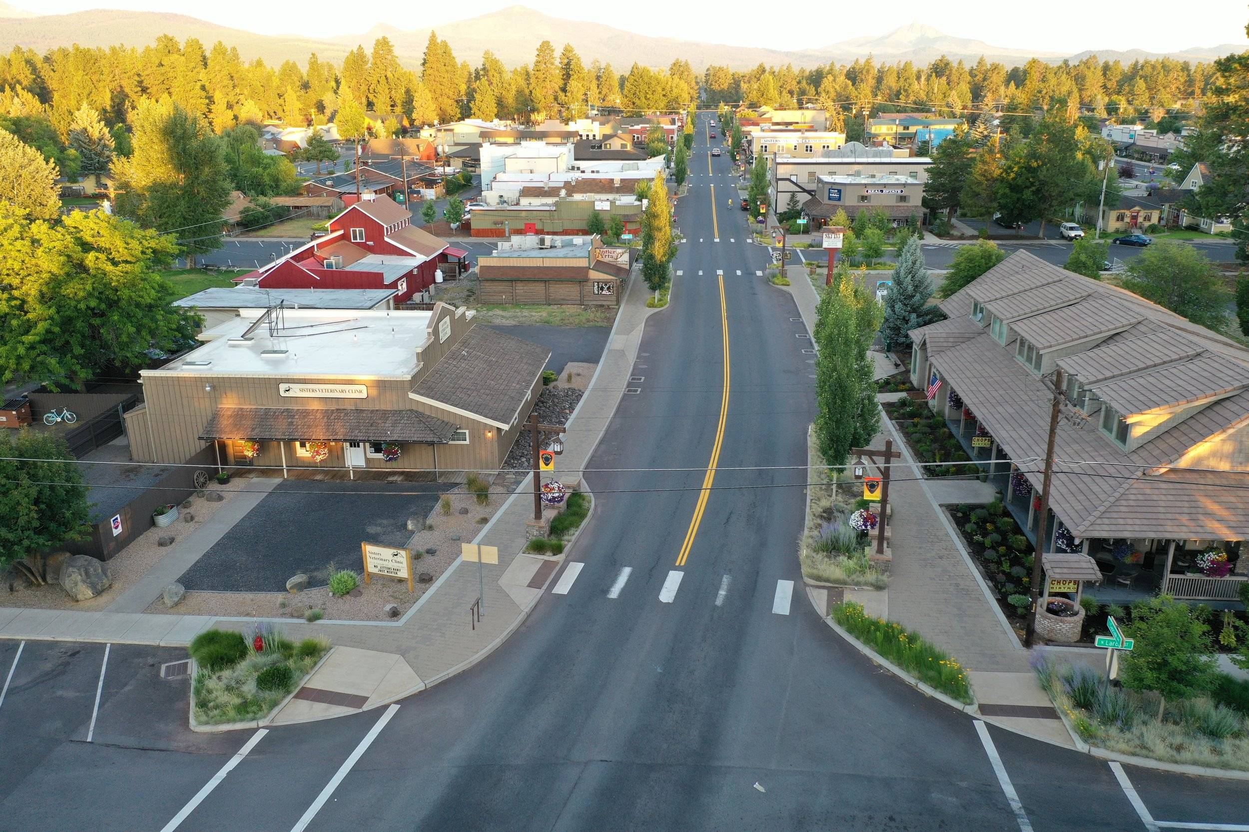 aerial image of cascade avenue in sisters with overexposed horizon, street curves away from view