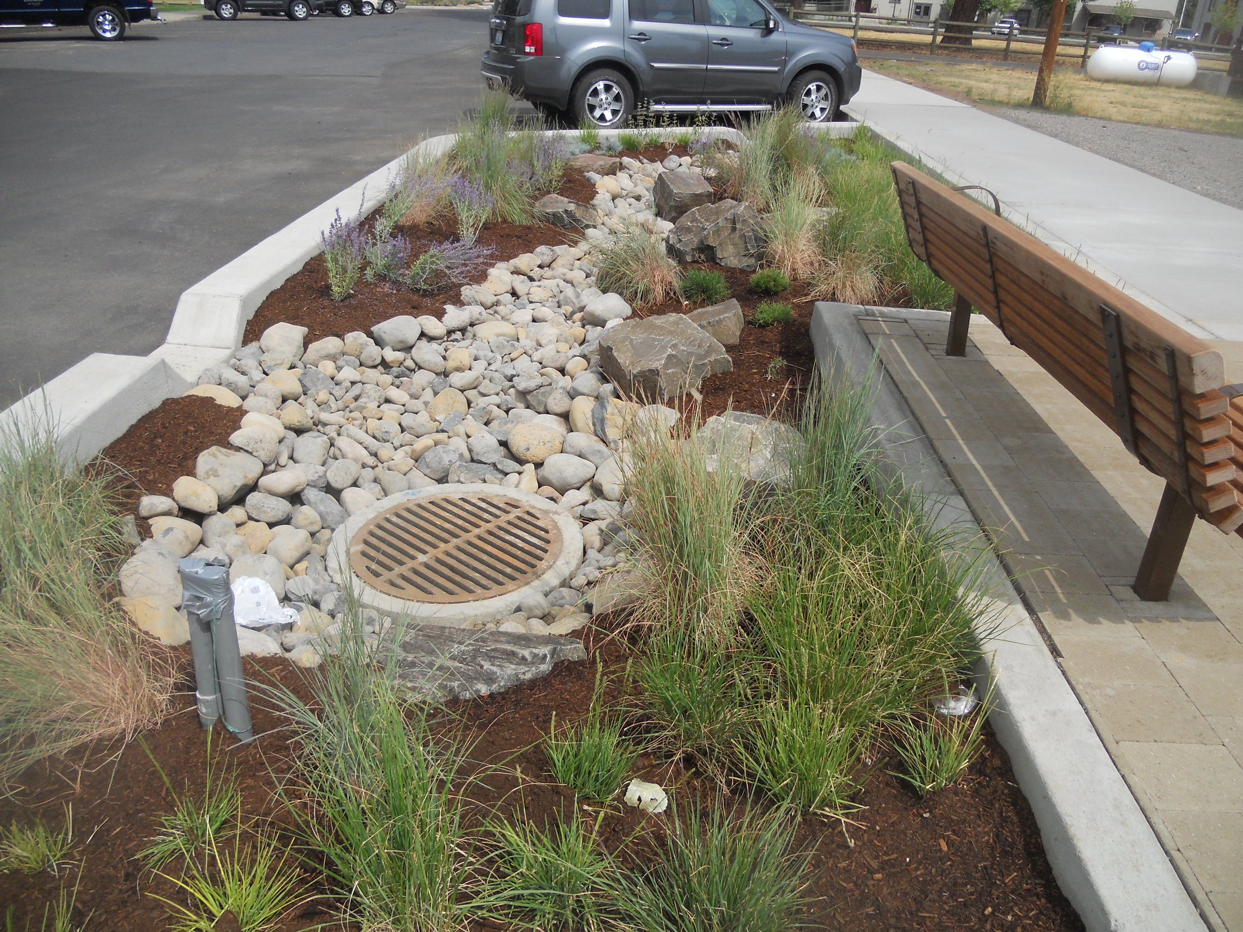 greenstreet stormwater swale with rocks and grasses along highway 20 in sisters, oregon