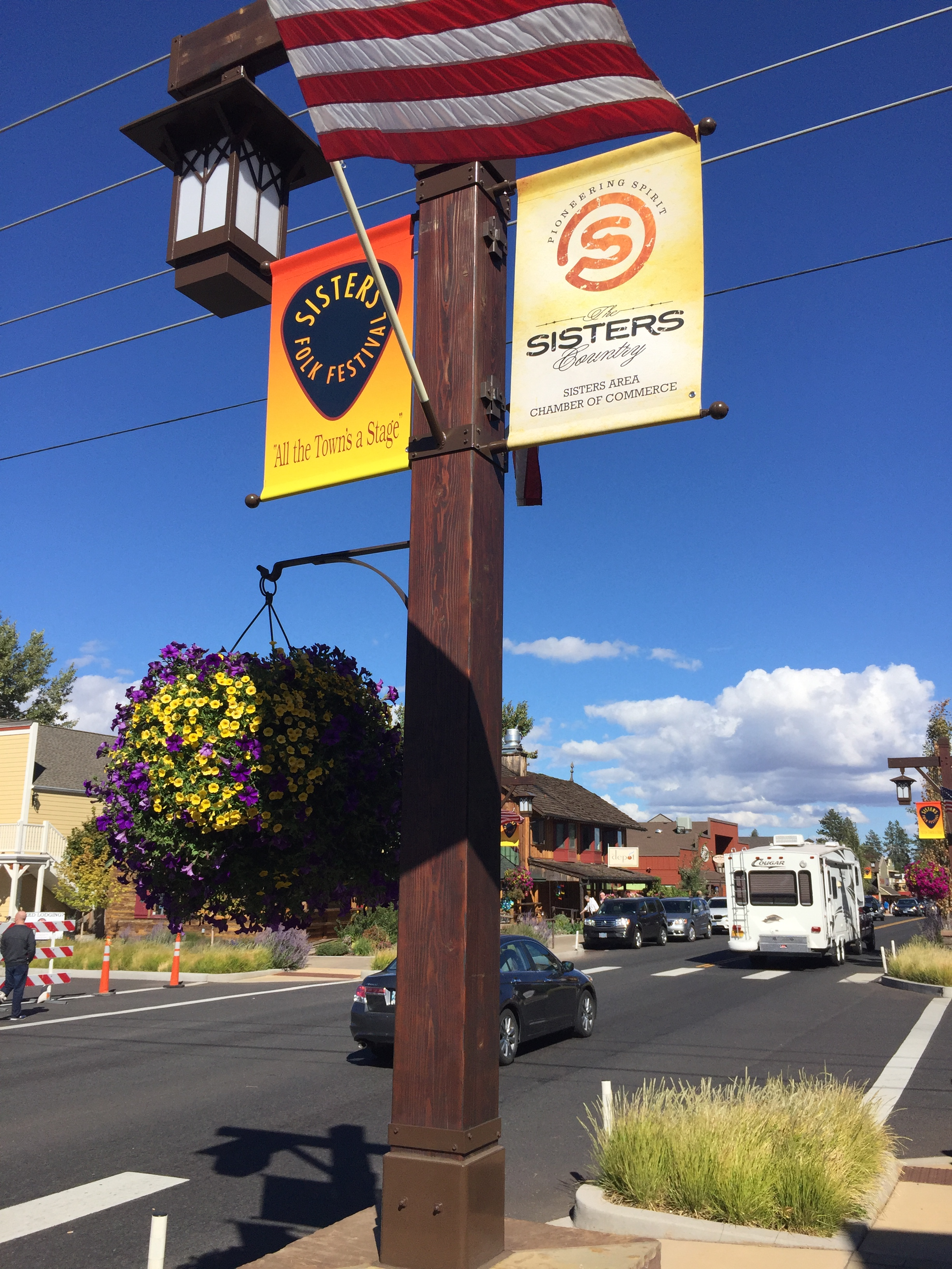 brightly colored signs hang from lamppost in downtown sisters along highway 20