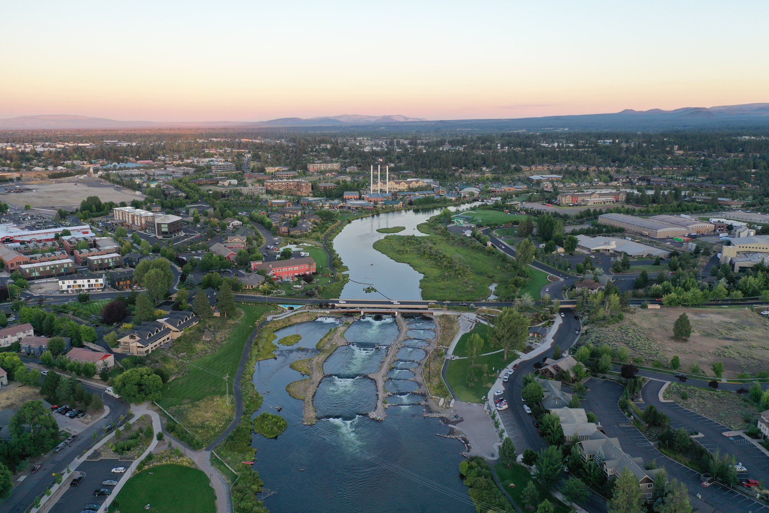 aerial image of deschutes river flowing through Bend, oregon, past the old mill district at sunset