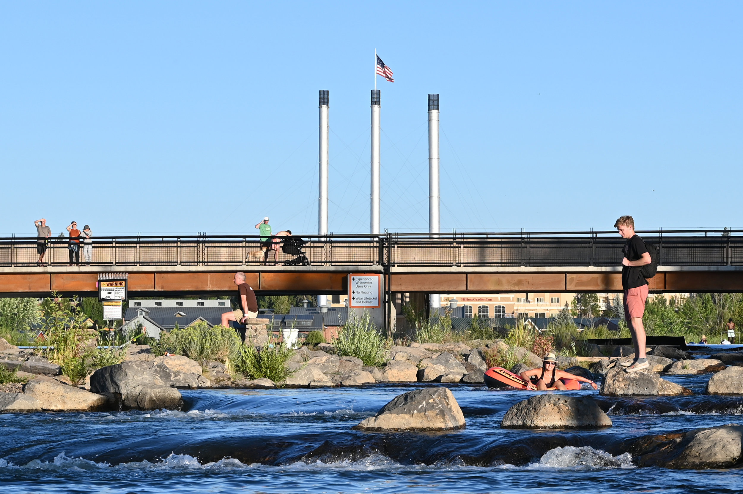 people line a pedestrian bridge above people in tubes and on rocks in the deschutes river, the old mill smokestacks in the background