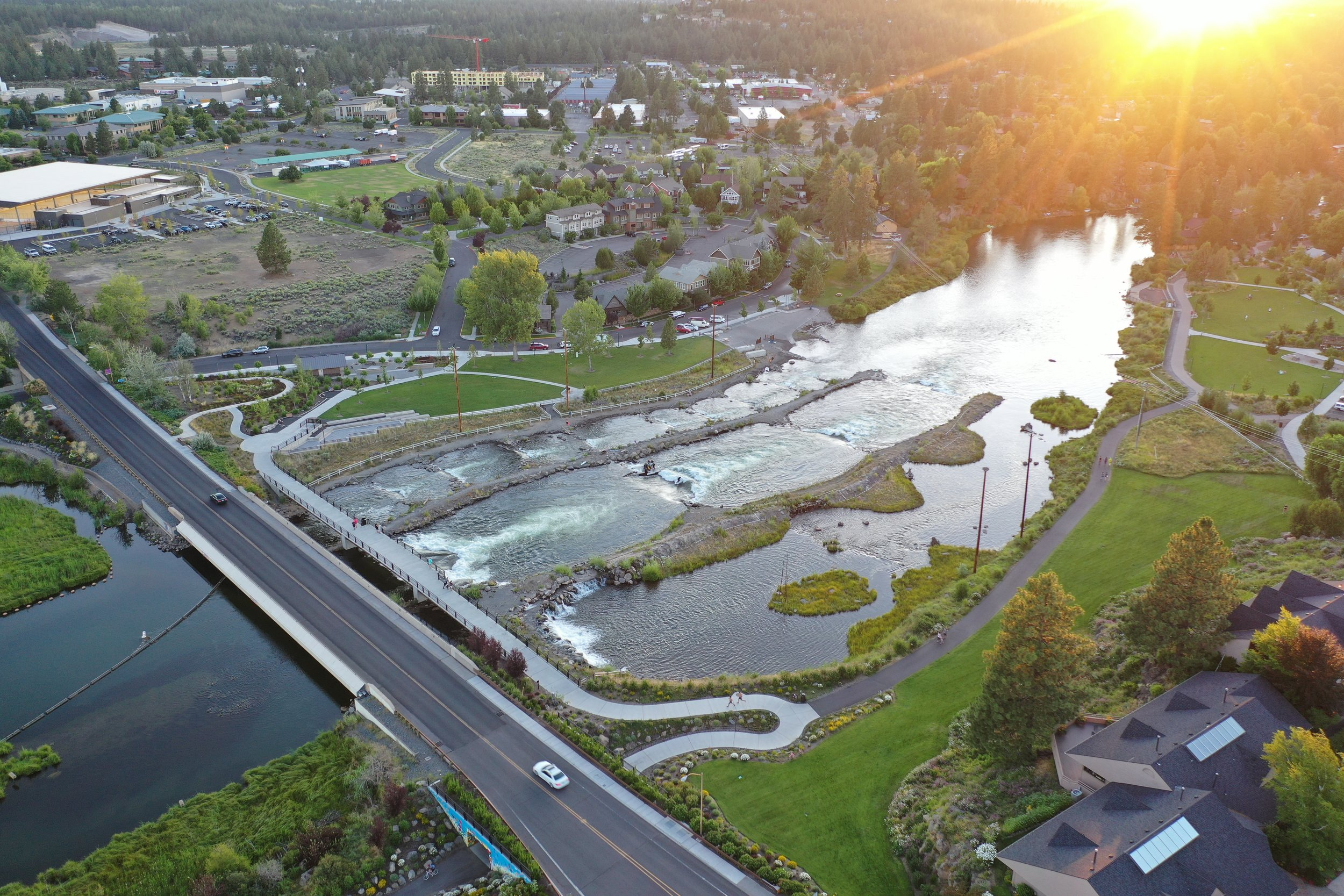 lens flare of sunset over whitewater park with river flowing