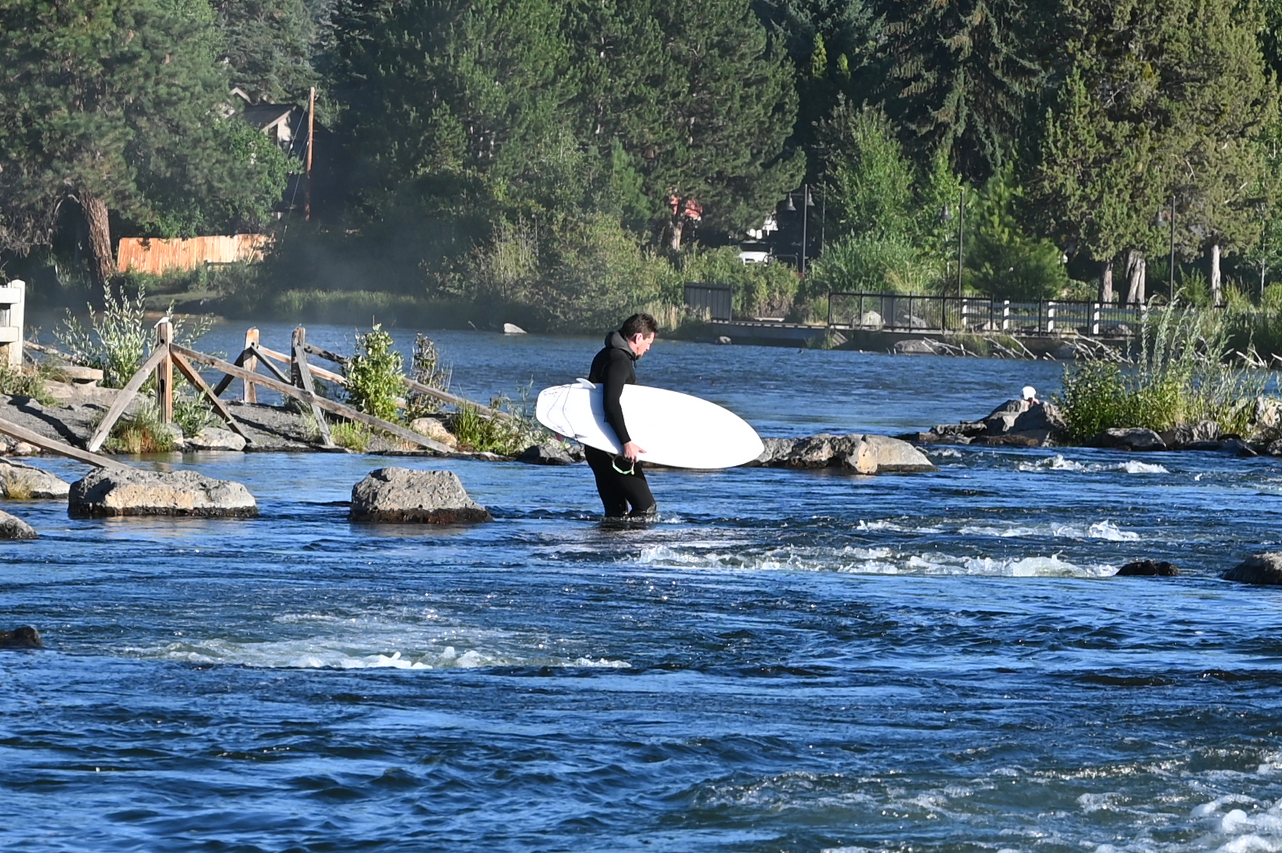a person holding a surfboard crosses a river with rocks in background